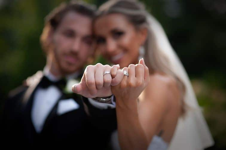 bride-and-groom-interlocking-fingers-showing-rings