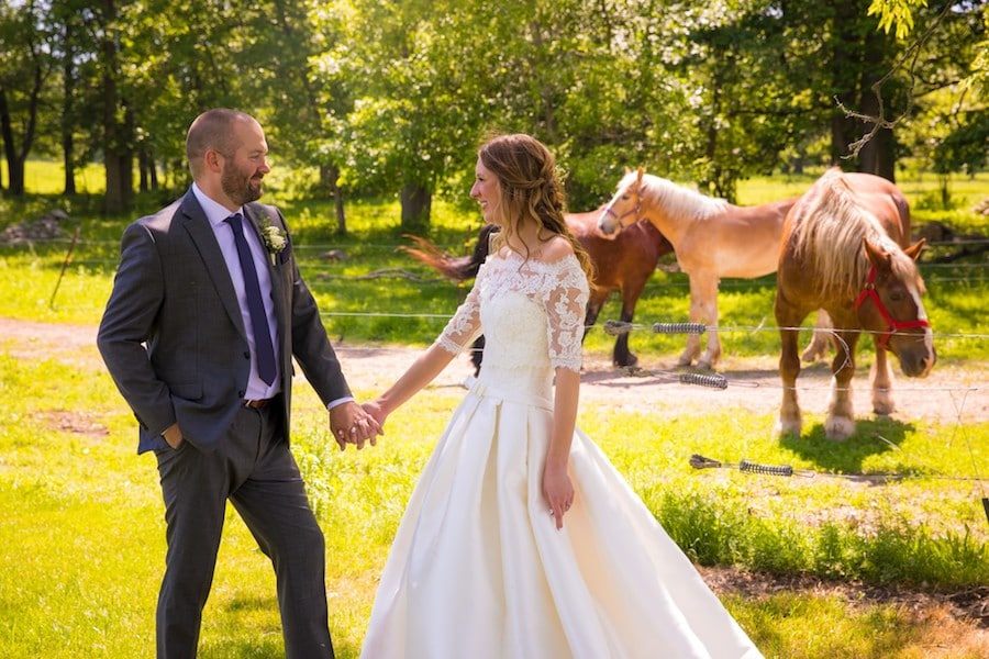 The Oakley Wedding Venue bride and groom with horses holding hands