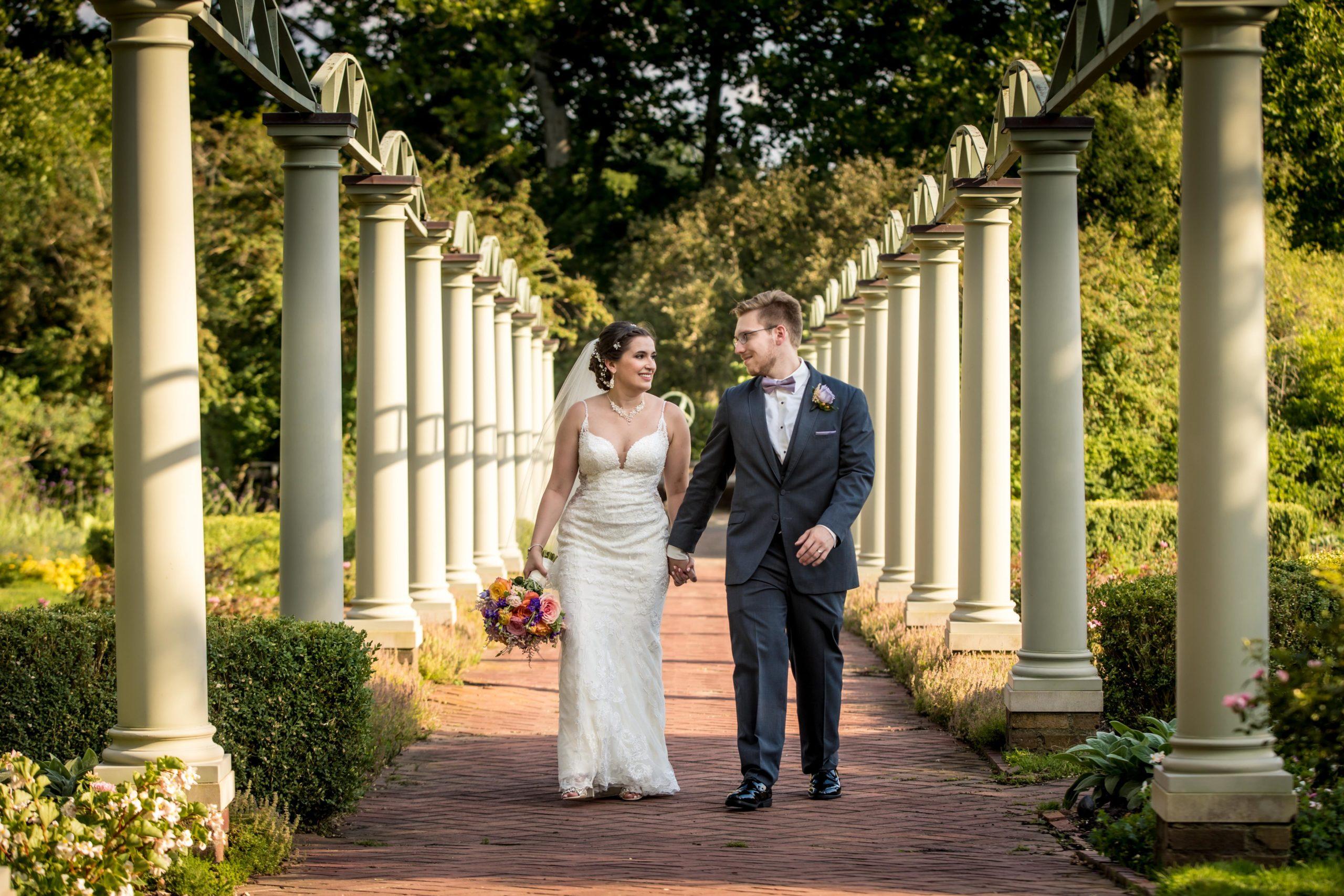 bride and groom walking in meadow brook garden