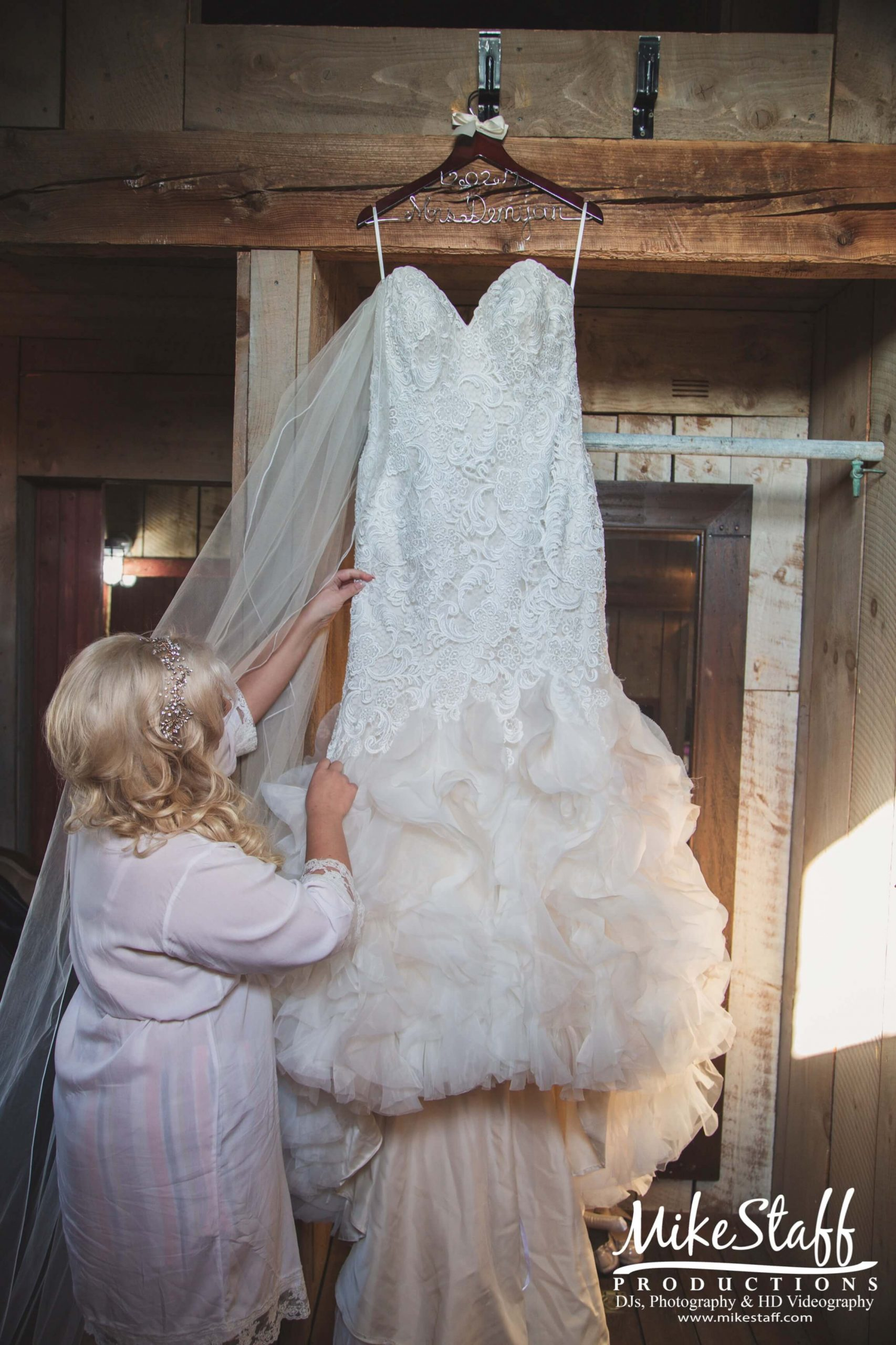 bride looking at dress hanging in barn