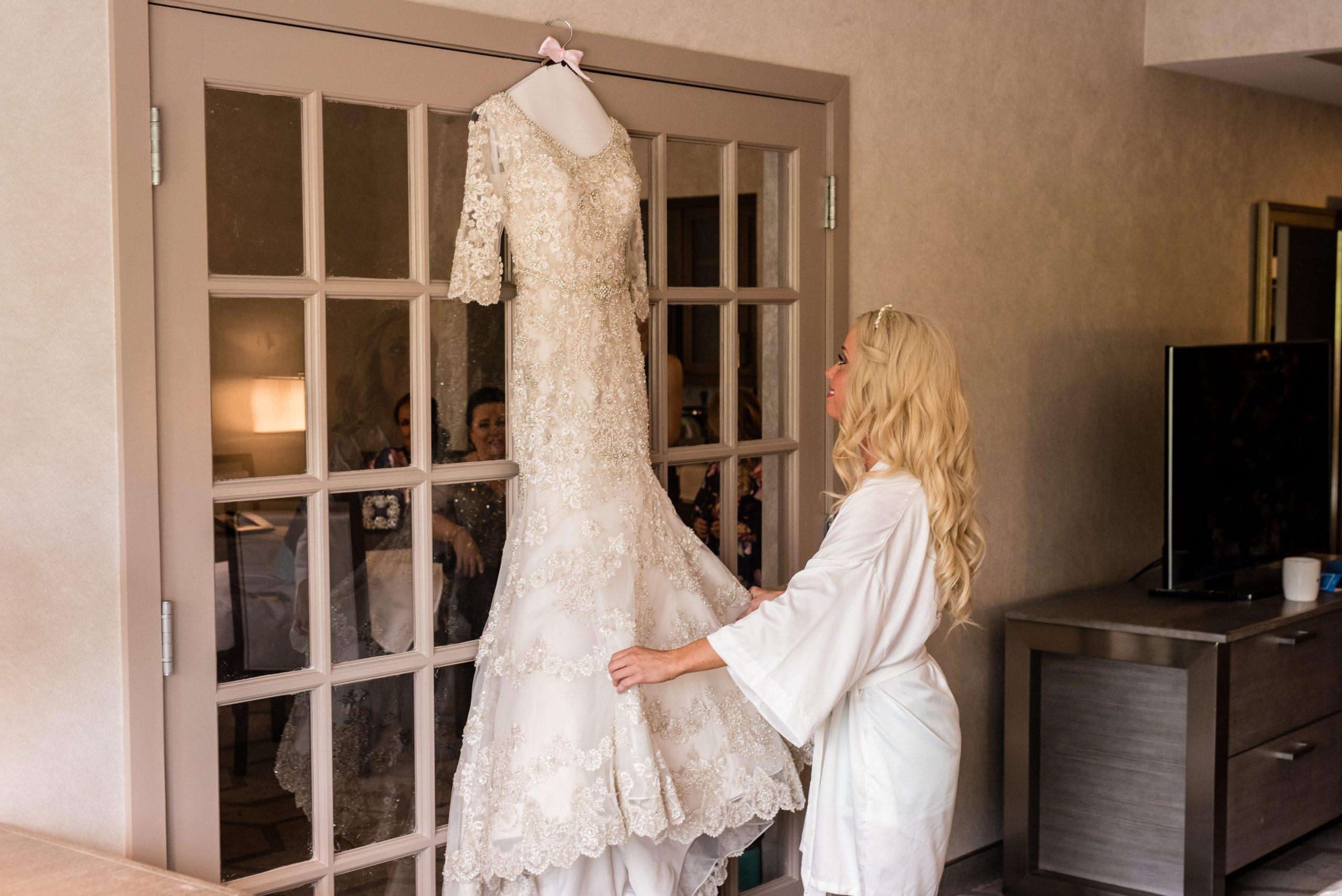 bride admiring her dress hanging on door