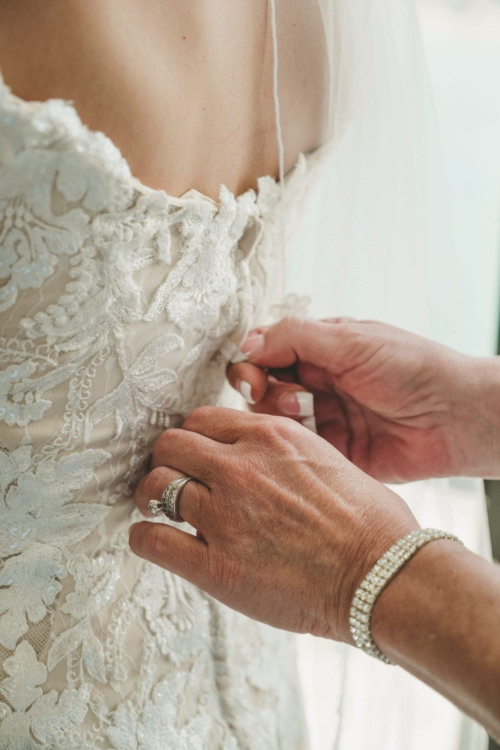 mother of bride zipping bride's gown