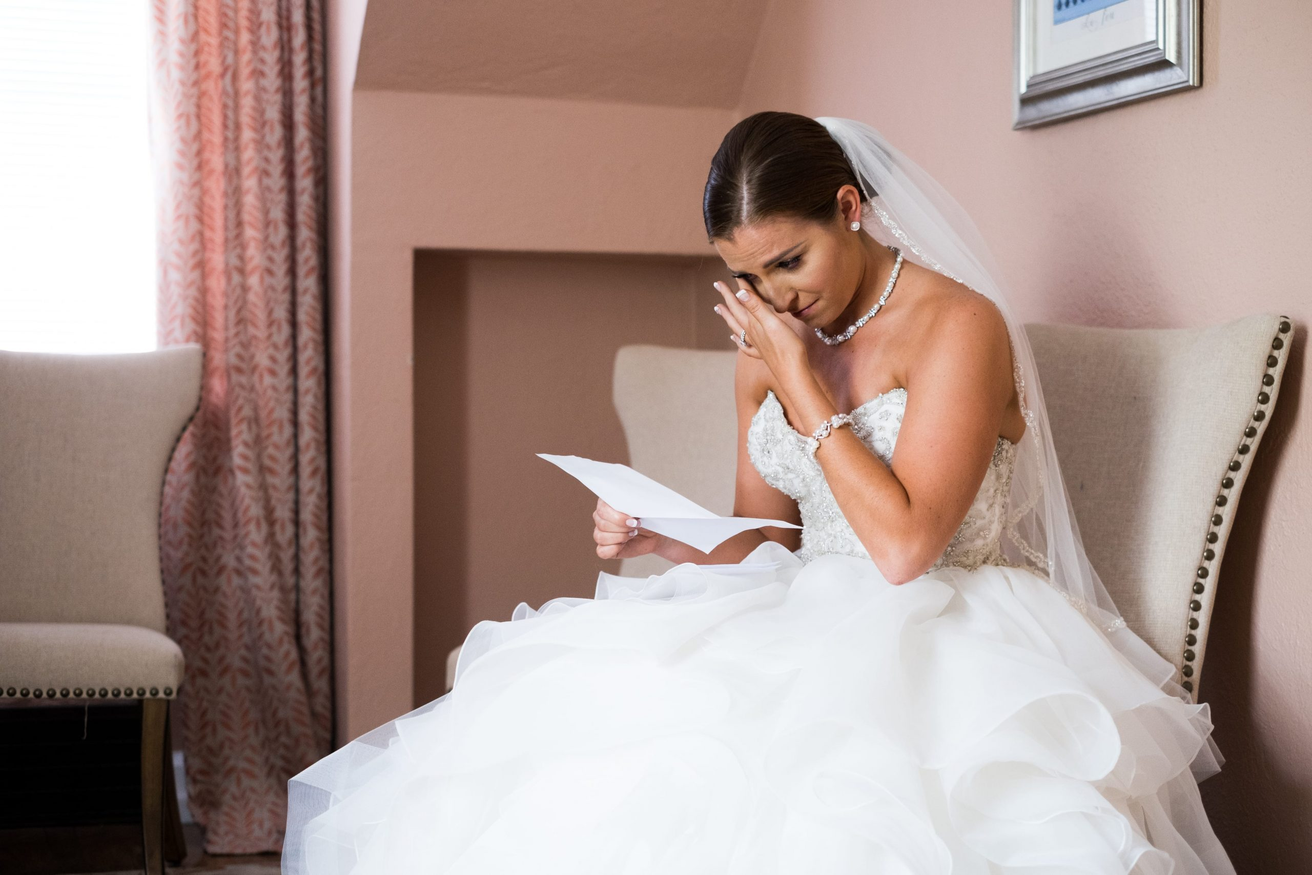 bride tearing up reading letter before ceremony