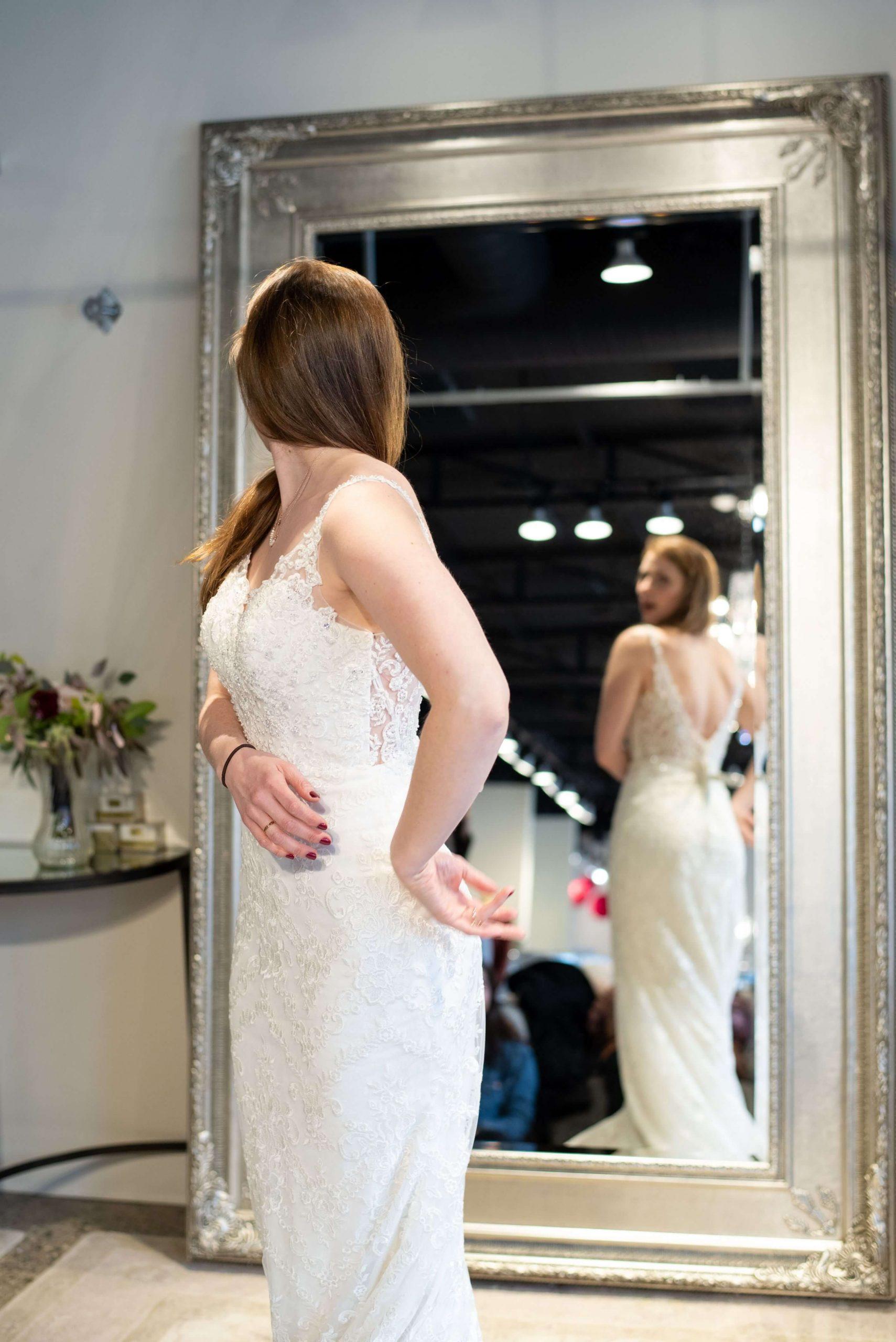 bride looking in mirror of wedding shoppe