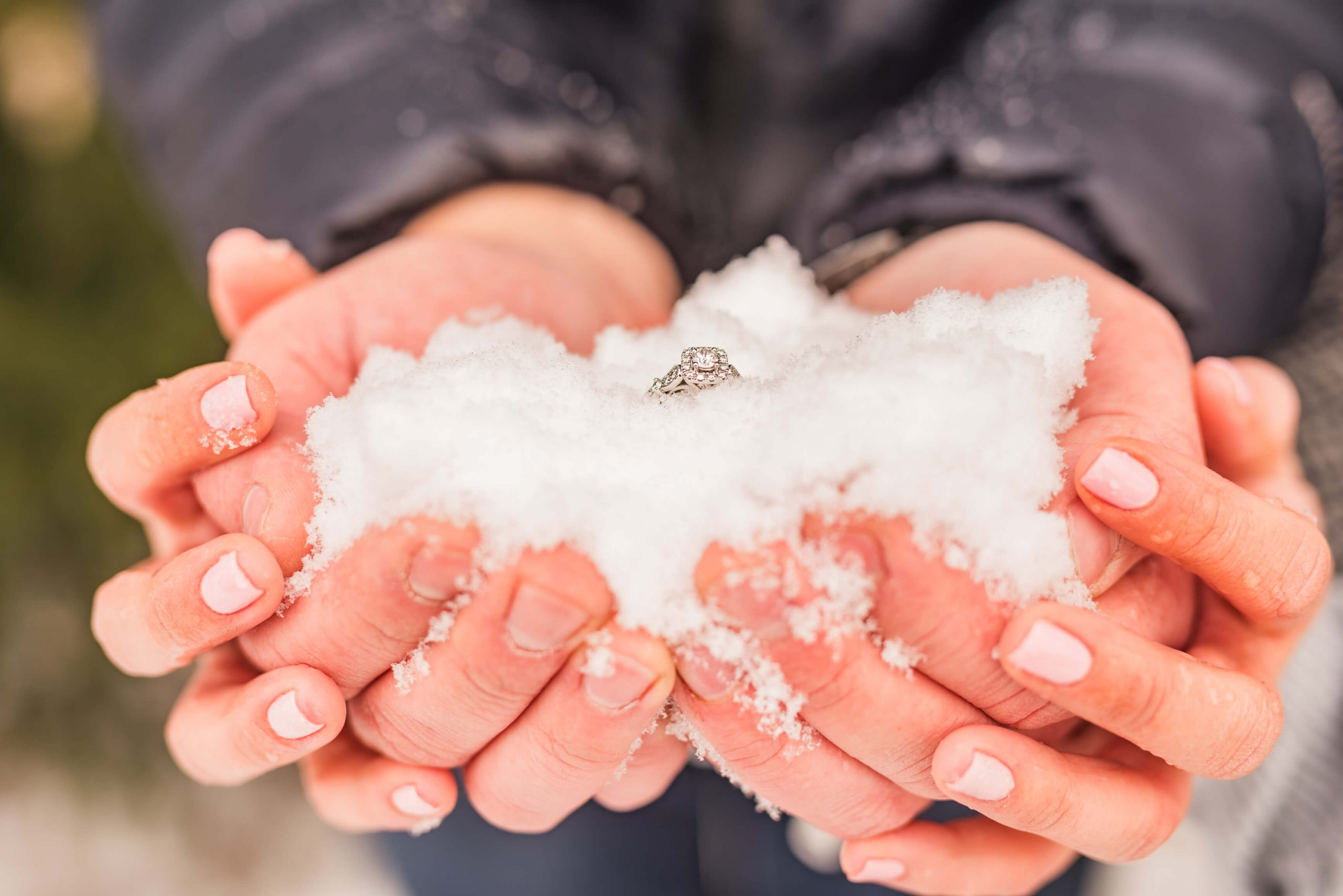 hands holding snow and engagement ring