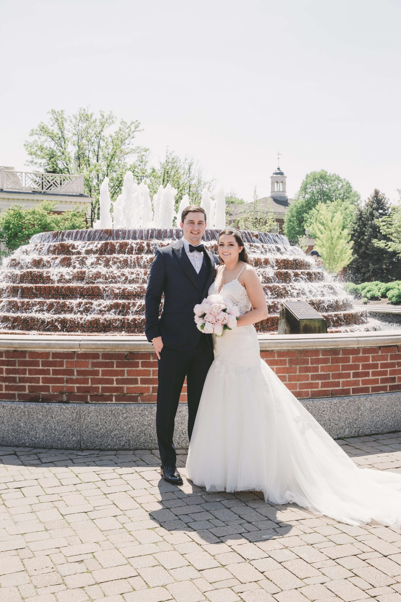 bride and groom standing in front of fountain