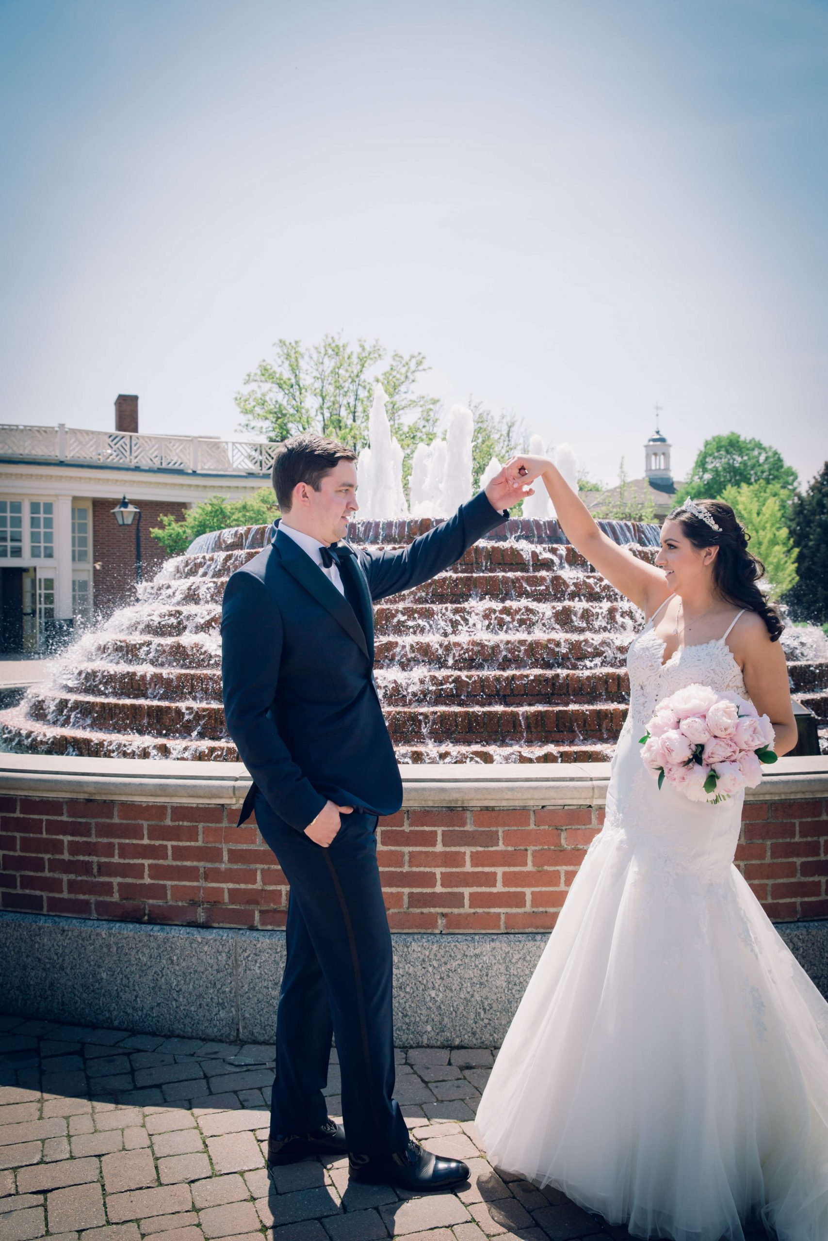 bride and groom dancing in front of fountain
