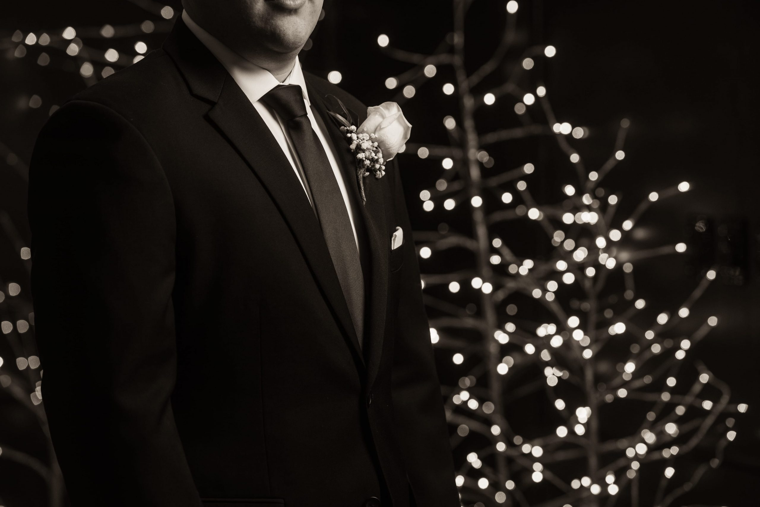 groom in front of Christmas trees