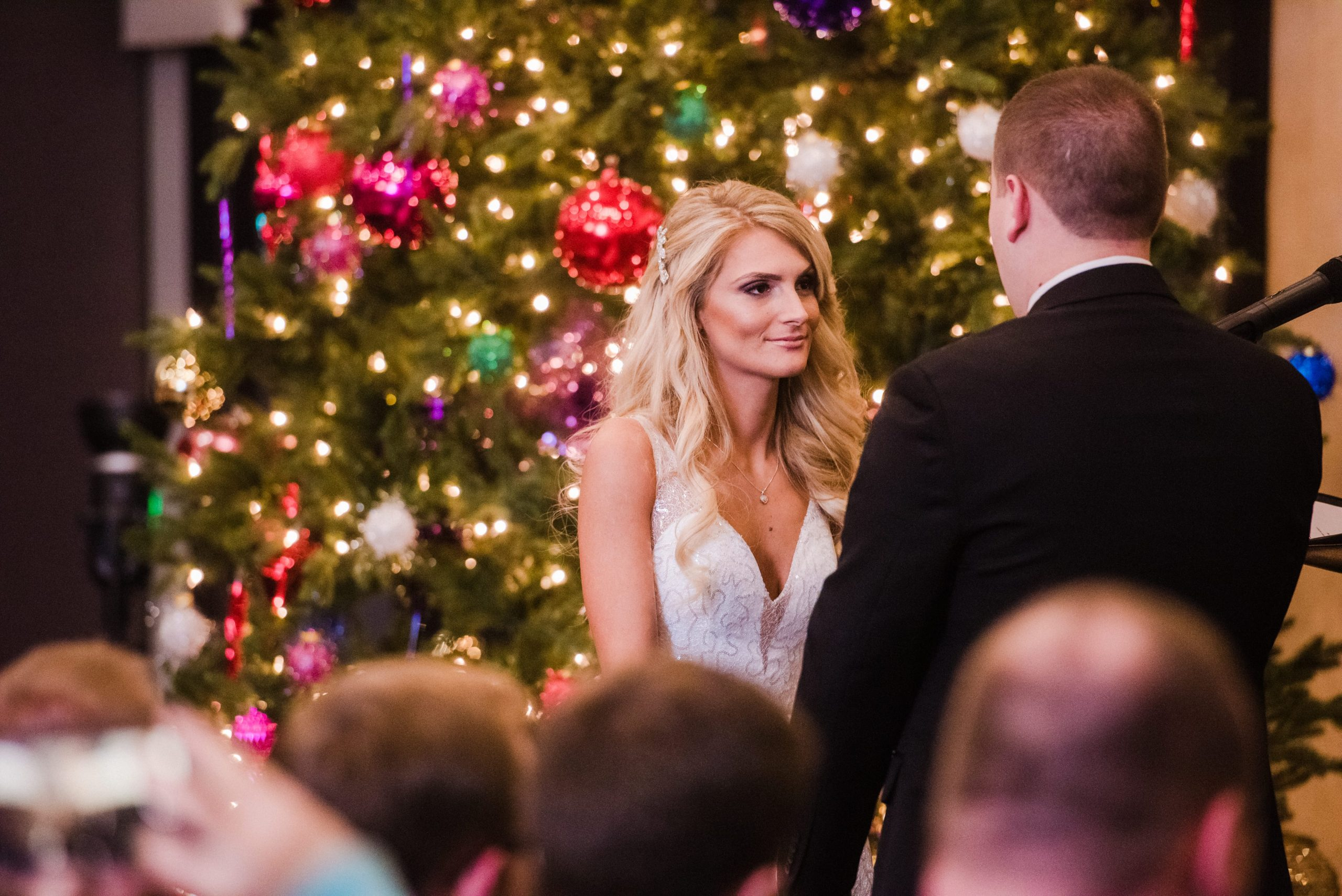 bride and groom in front of Christmas tree