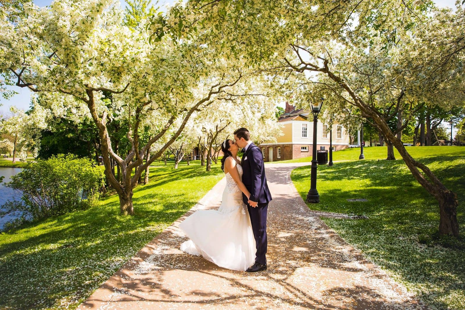 bride and groom kissing on path at greenfield village