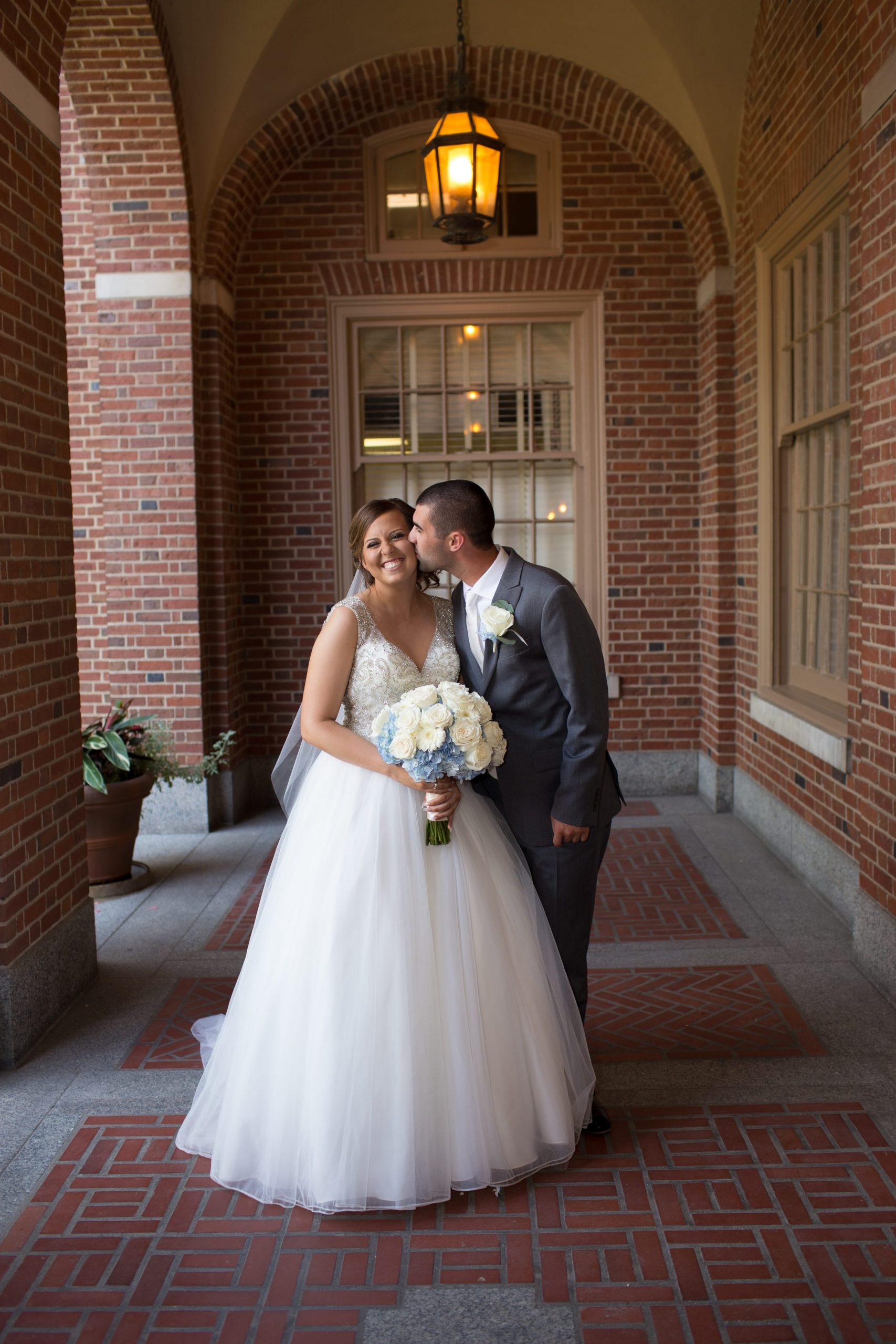 groom kissing bride on cheek under brick archway
