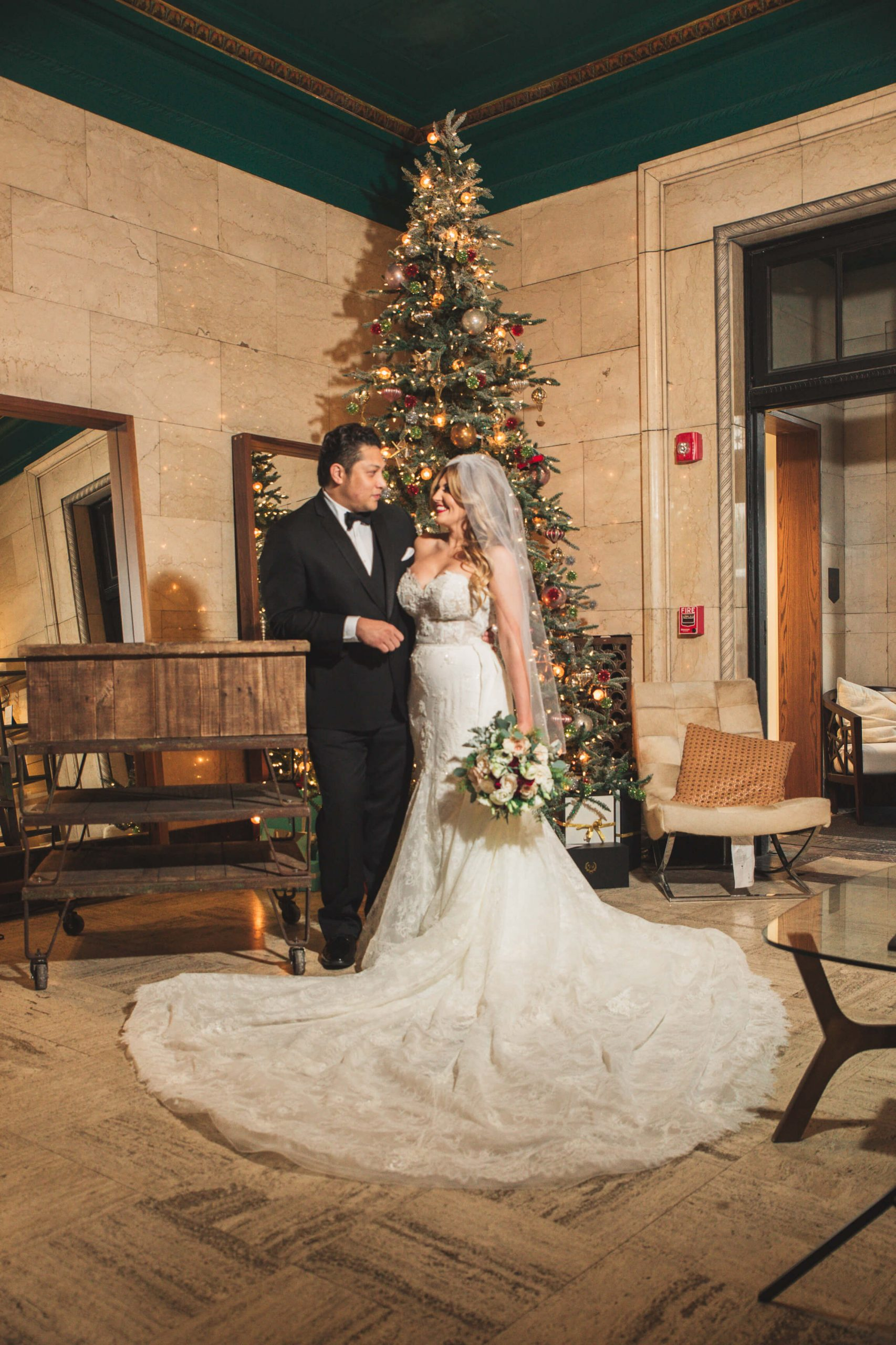 bride and groom romantic in front of Christmas tree