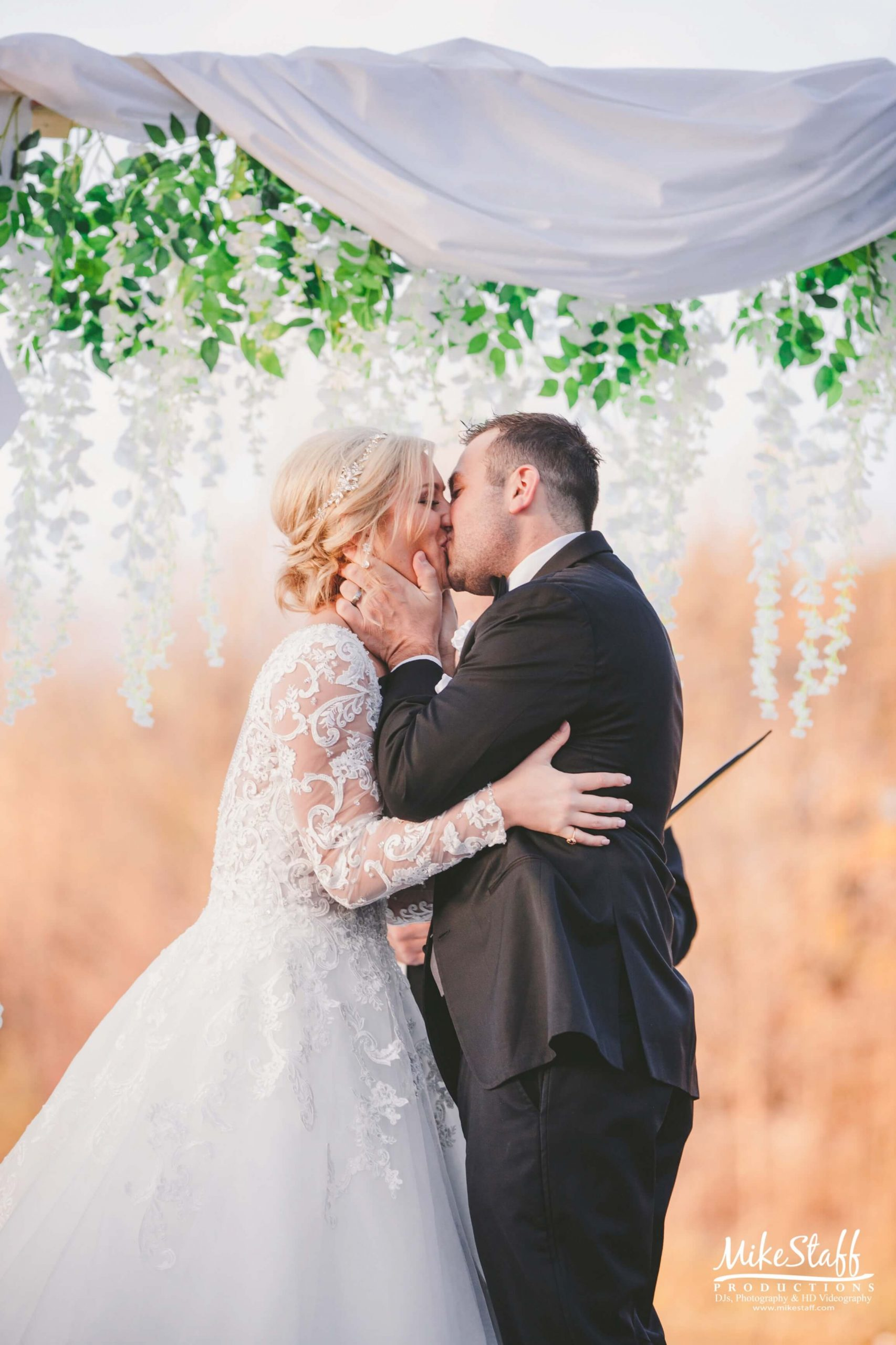 bride and groom kissing at alter