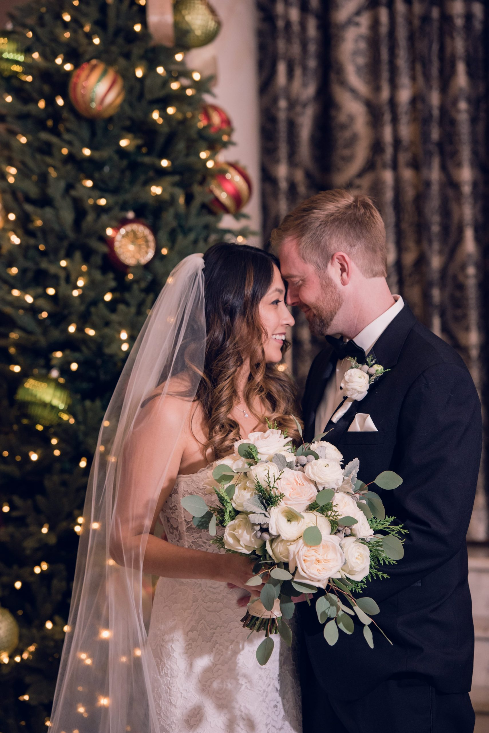 bride and groom by Christmas tree