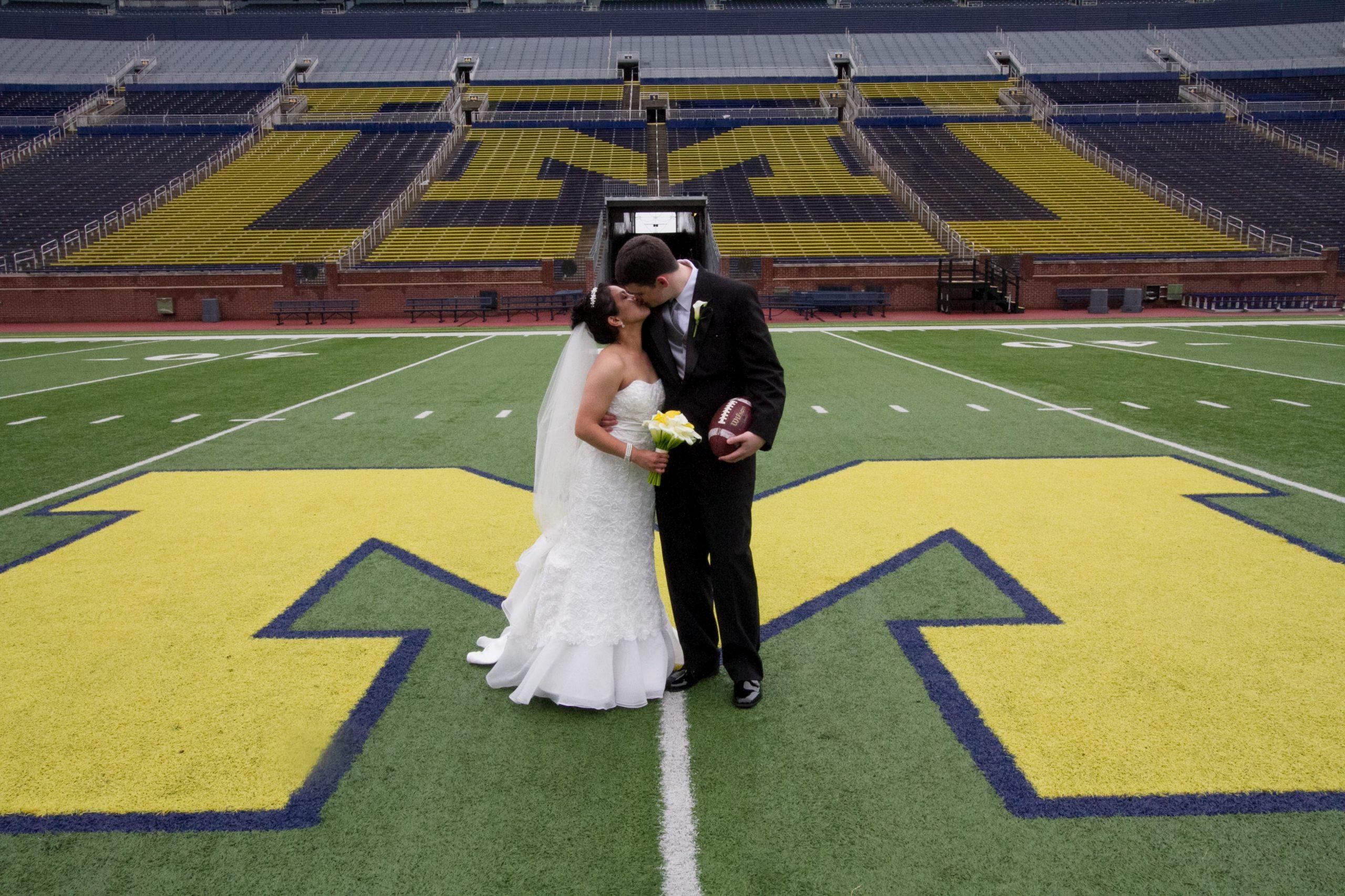 bride and groom kissing michigan stadium