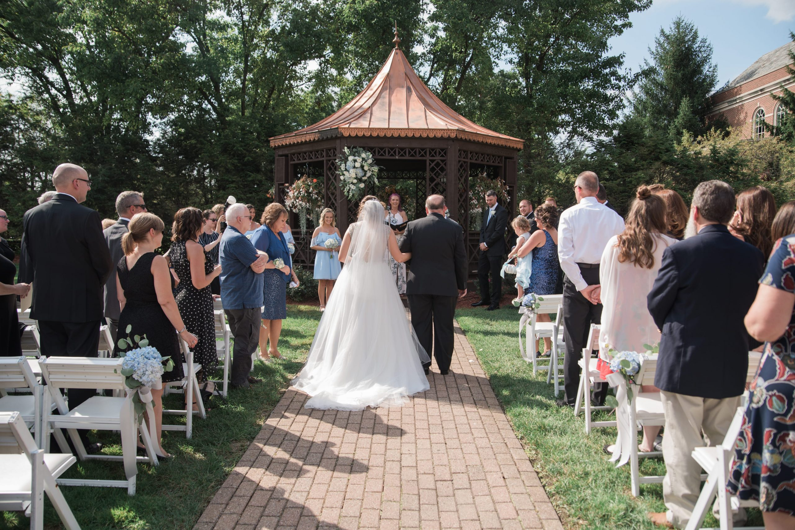 bride walking down aisle with father at outdoor ceremony