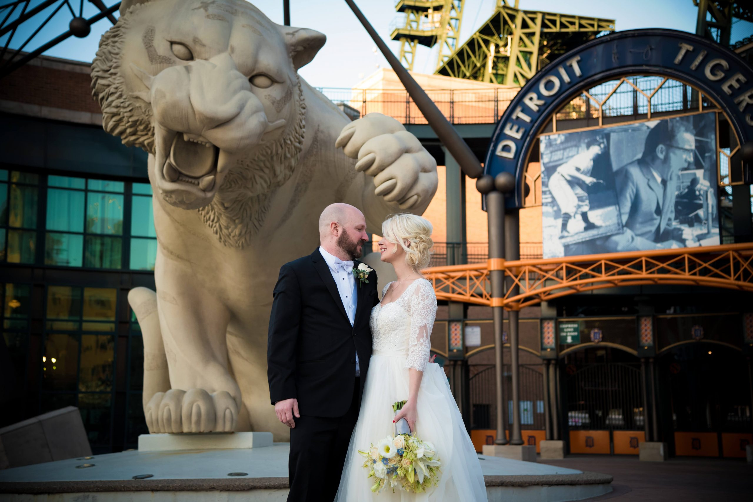 bride and grooms kissing in front of comerica park