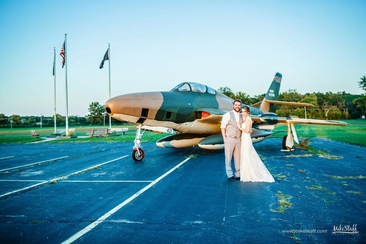 bride and groom with military plane