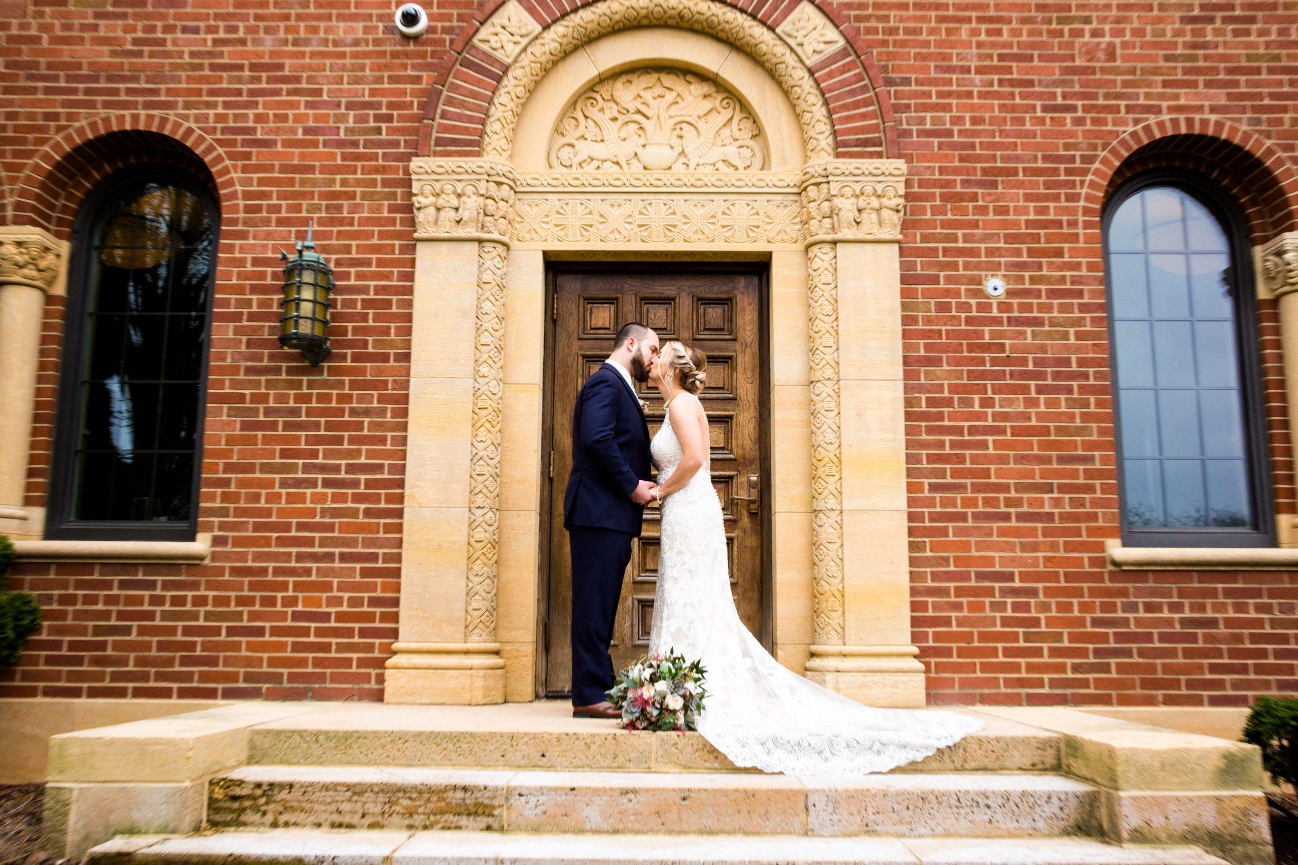 bride and groom kissing outside inn at st. john's