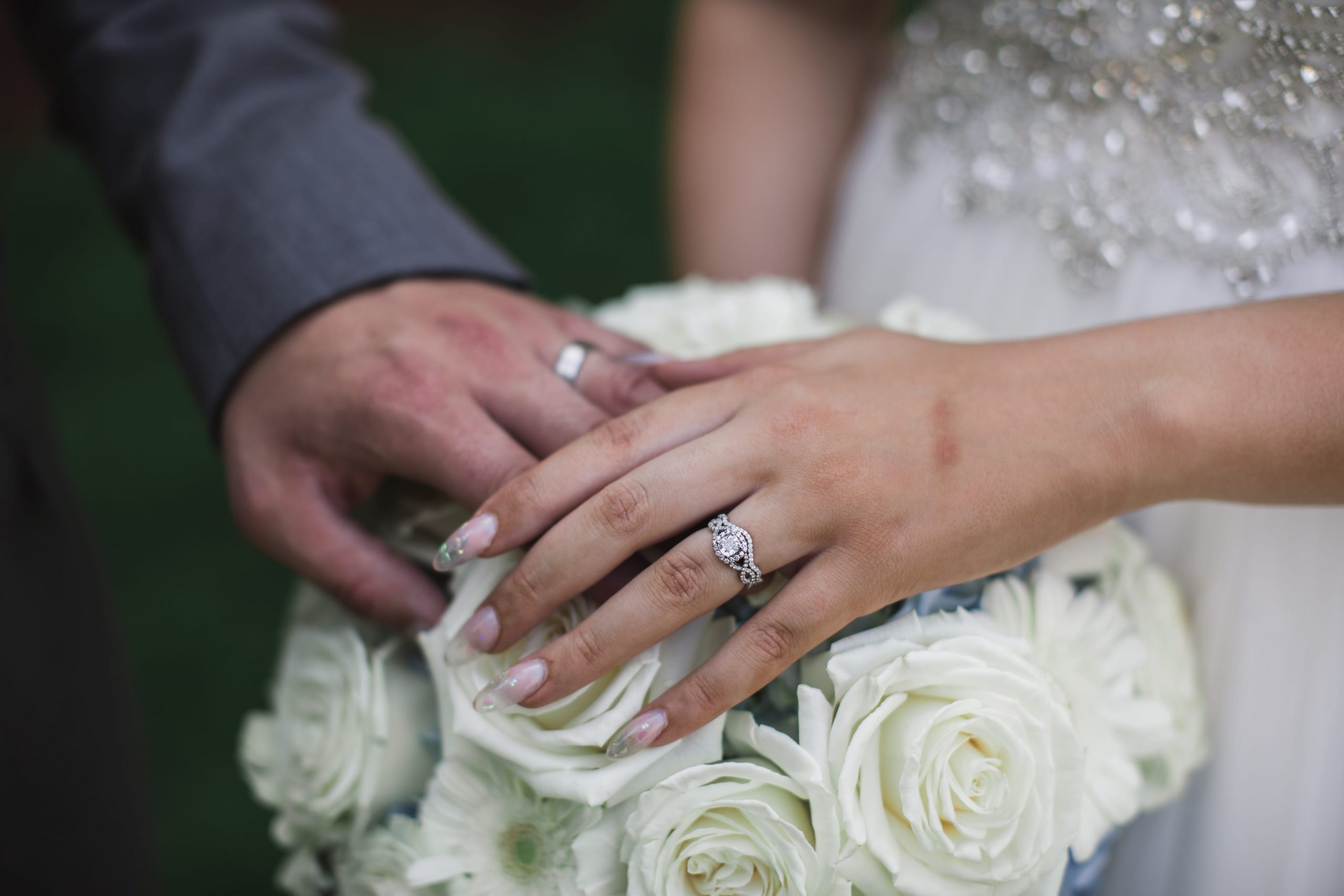 bride and groom's hands on bridal bouquet
