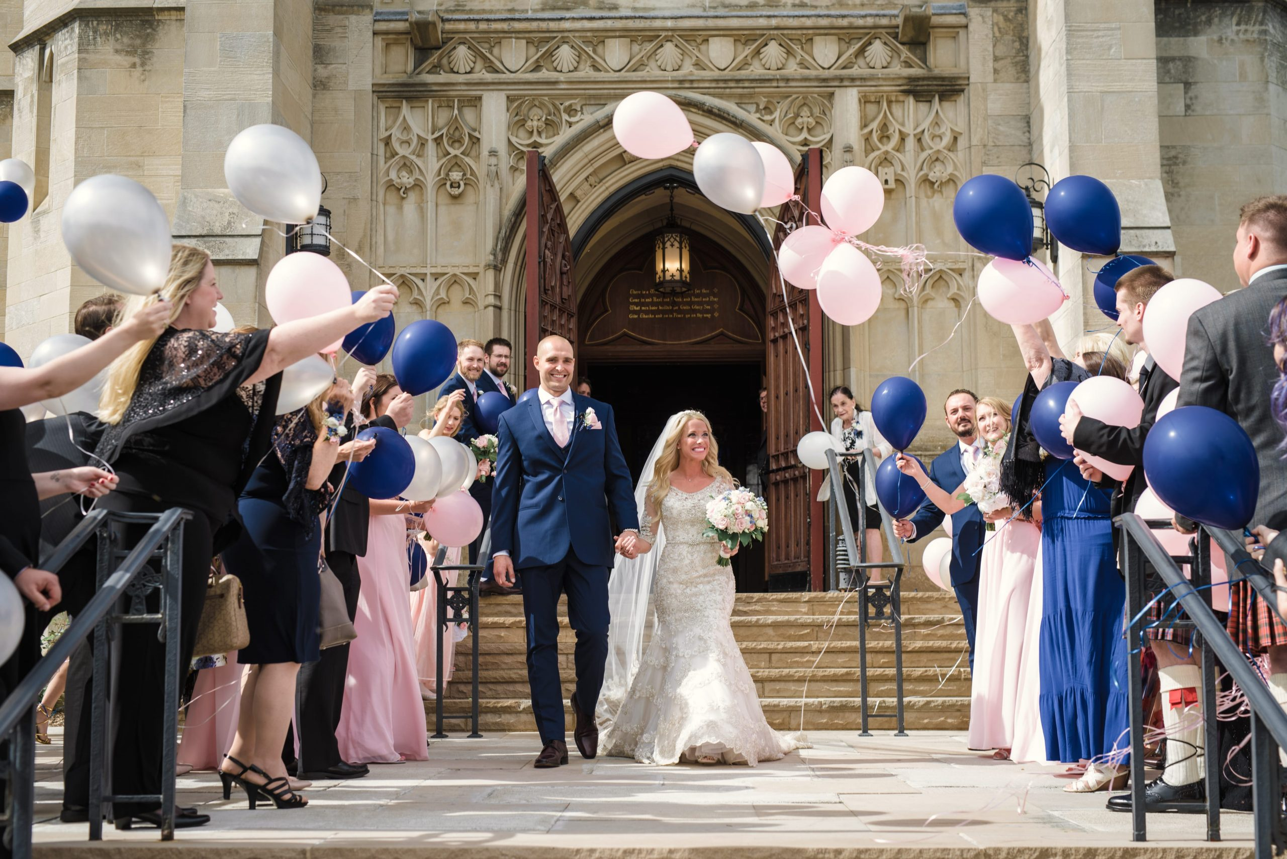 bride and groom leaving church with guests holding balloons