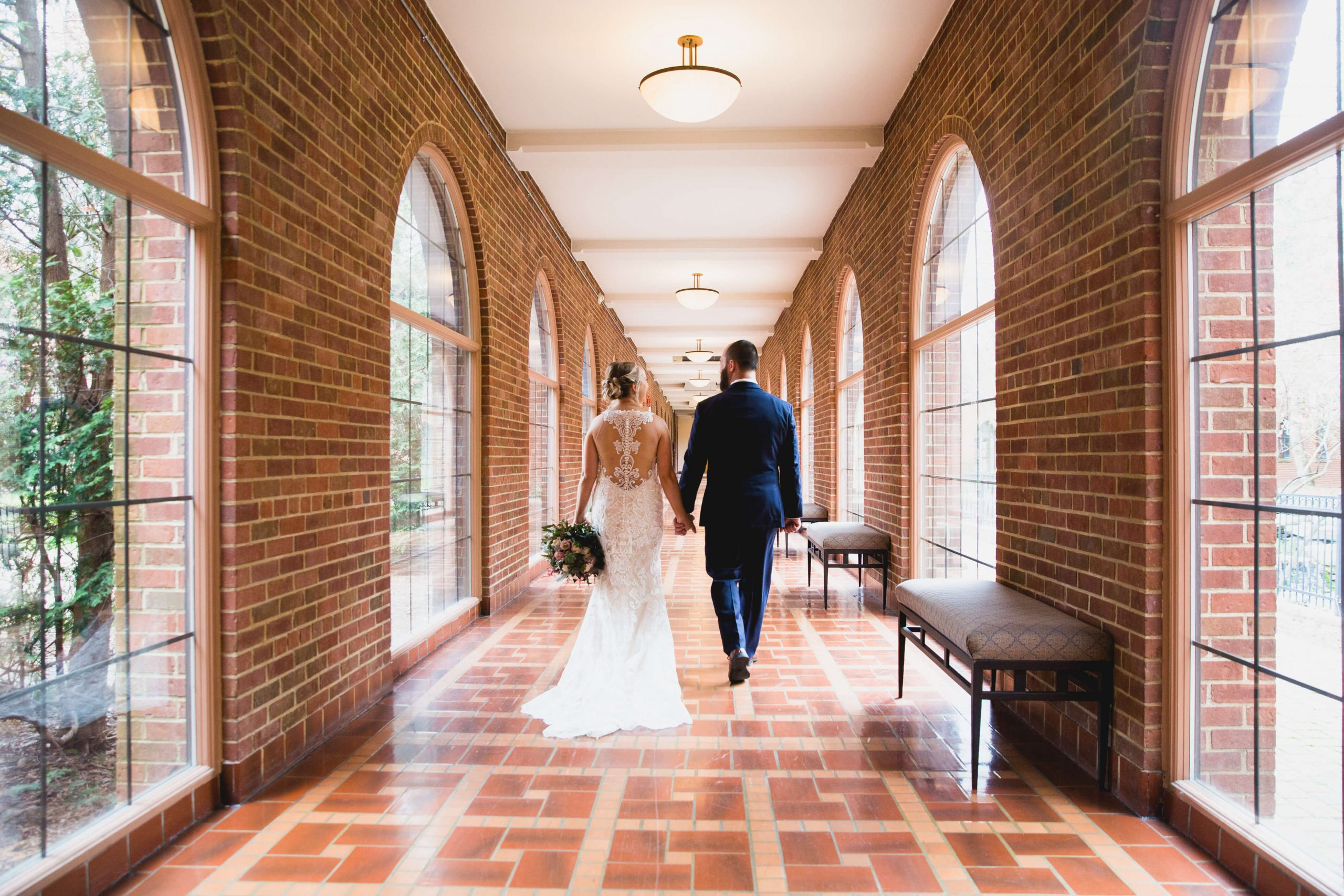 bride and groom walking down hall at inn at st. john's
