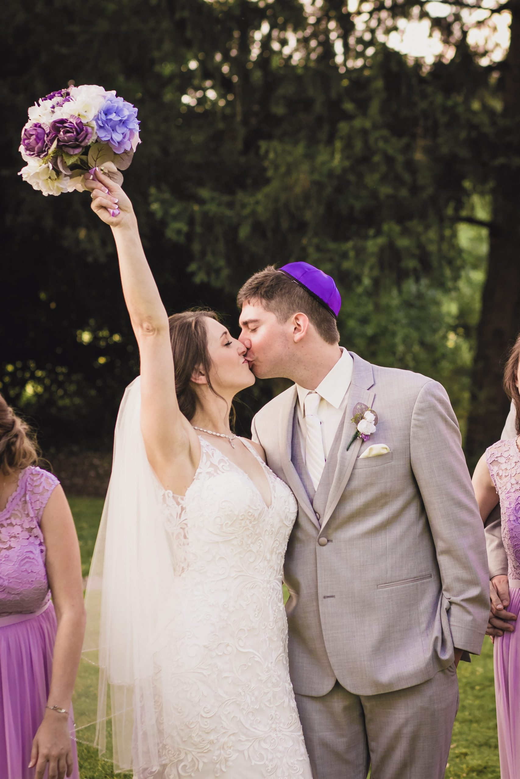 bride kissing groom while holding bouquet in the air