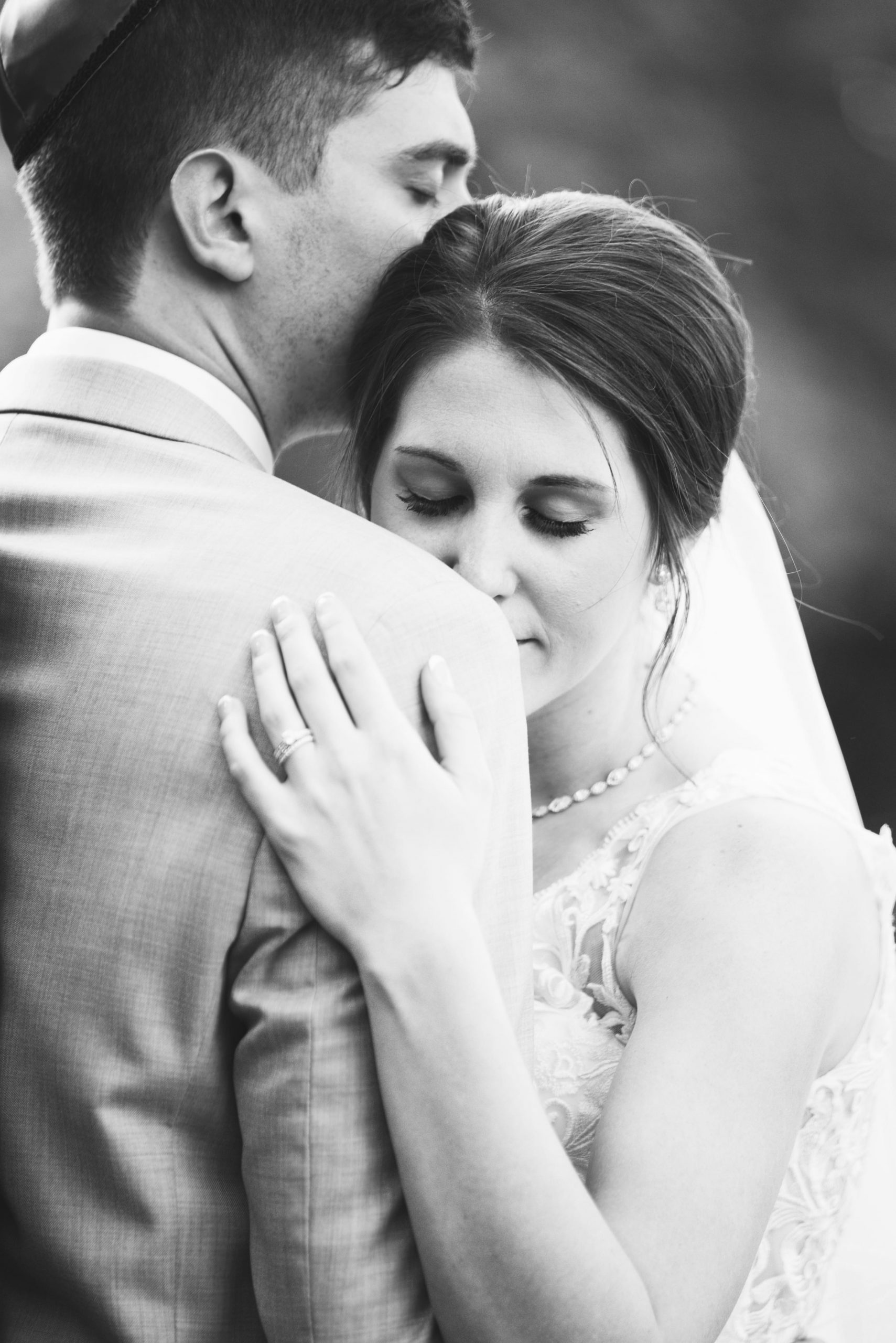 black and white photo of bride leaning on groom's shoulder
