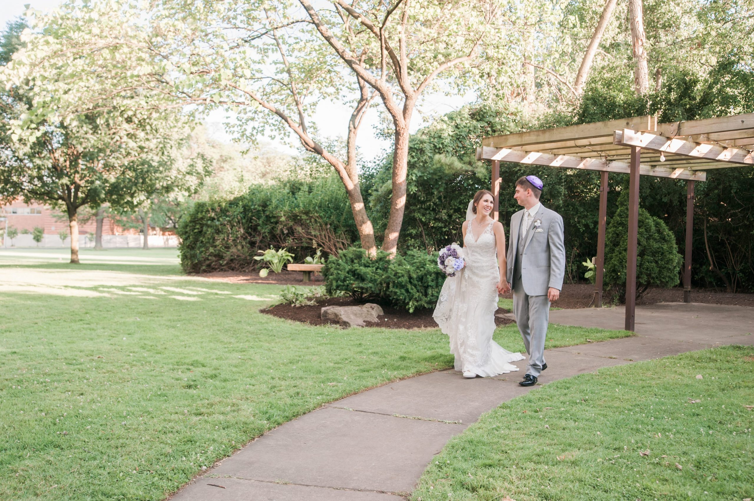 bride and groom walking under pergola
