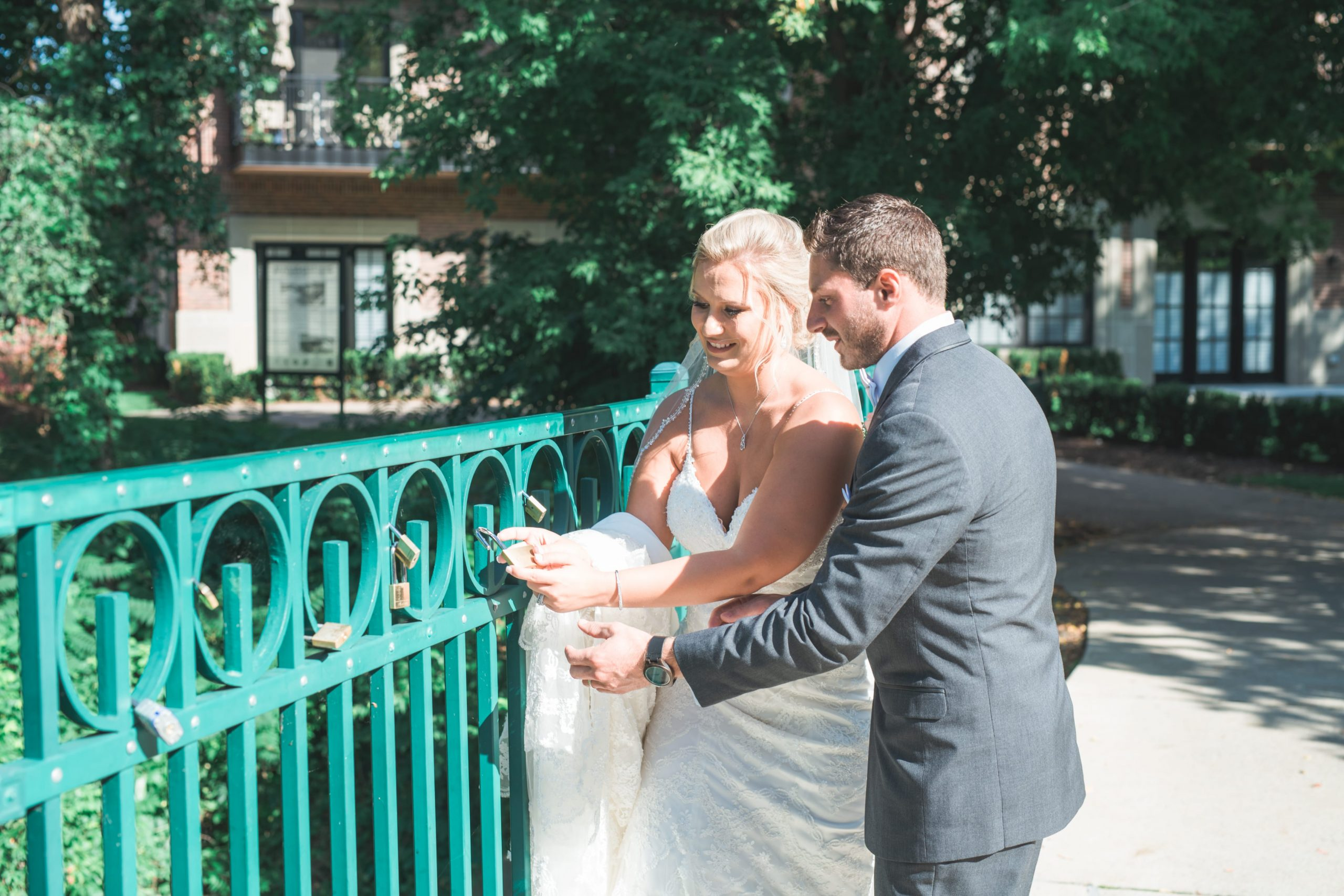 bride and groom putting lock on a fence