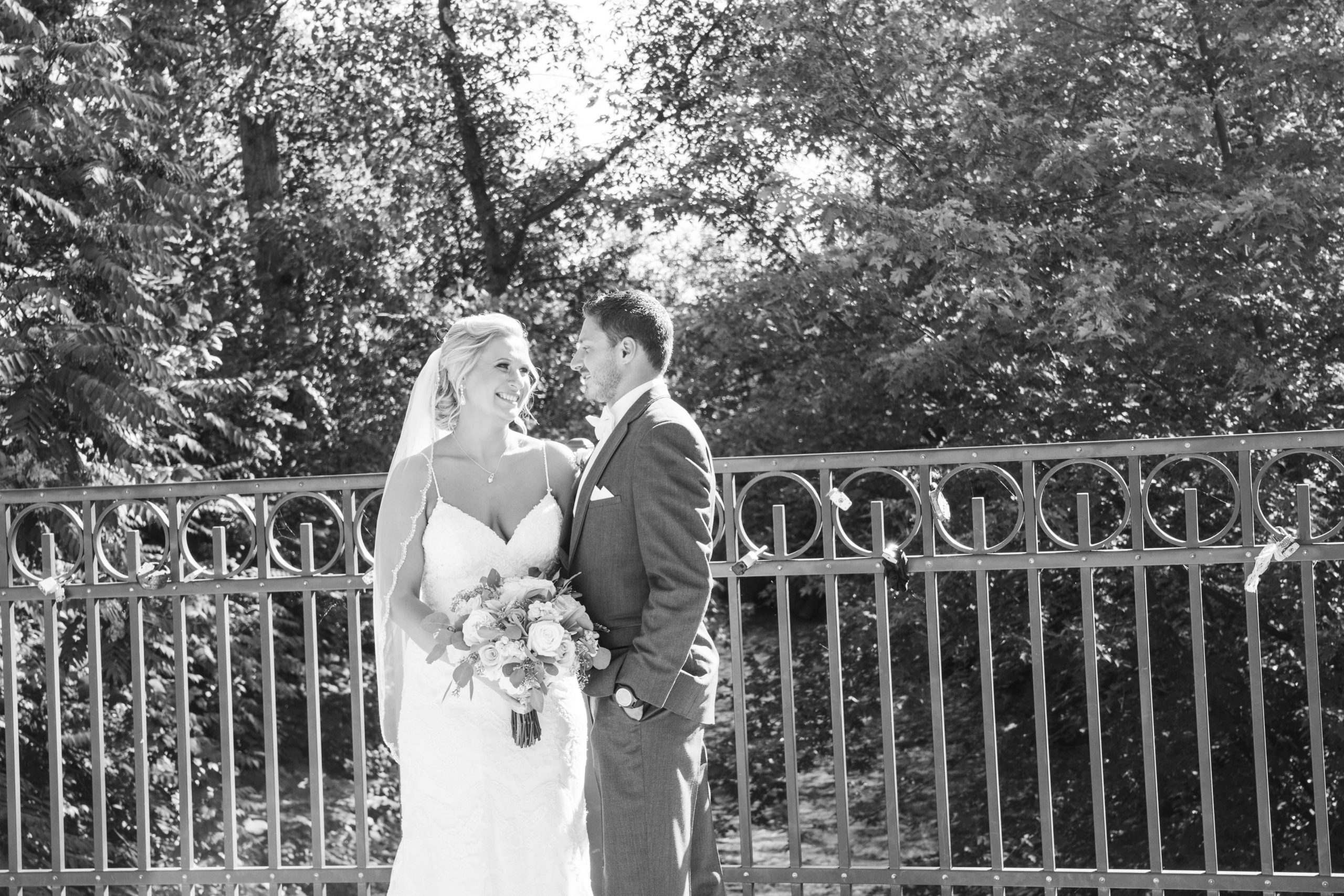 bride and groom looking at each other on bridge
