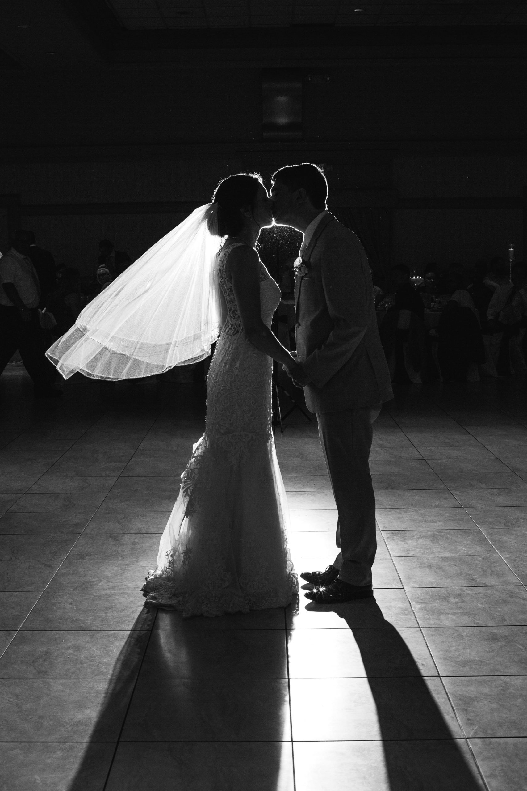 bride and groom kissing on dancefloor with spotlight