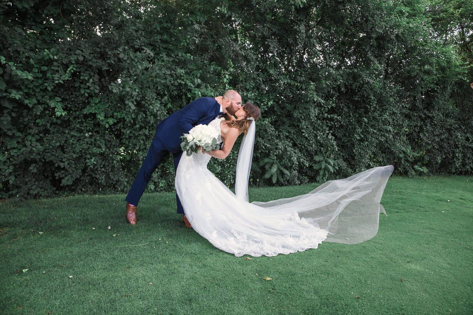 groom dipping bride while kissing her outside