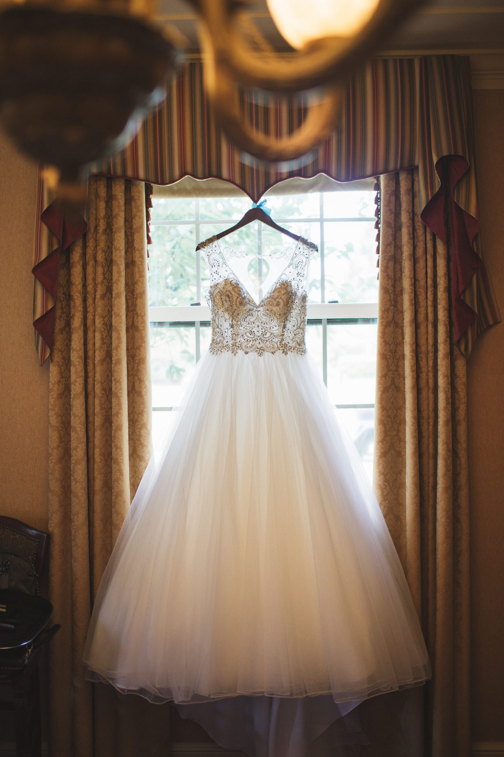 dress hanging from window with dramatic lighting