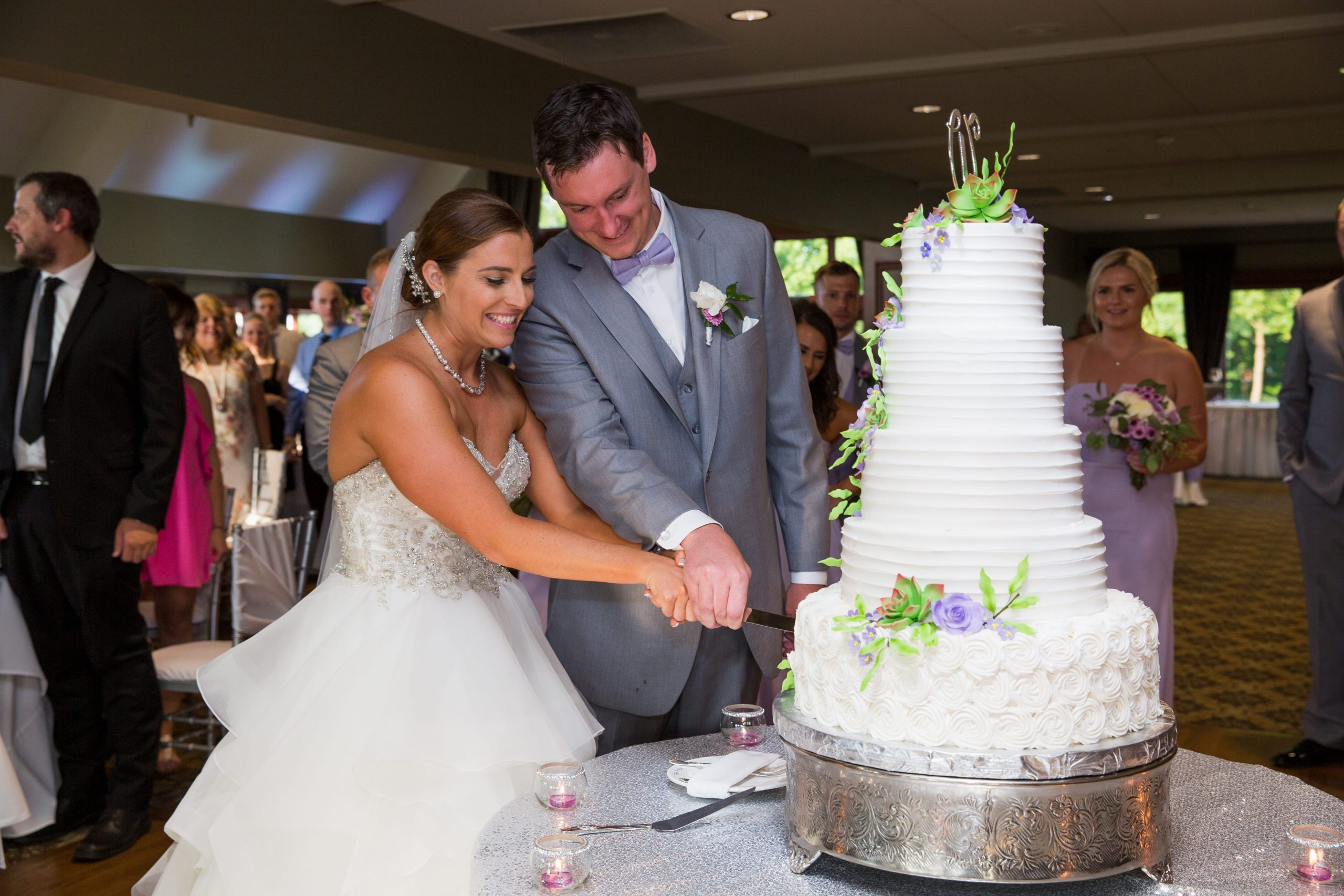 bride and groom smiling while cutting wedding cake