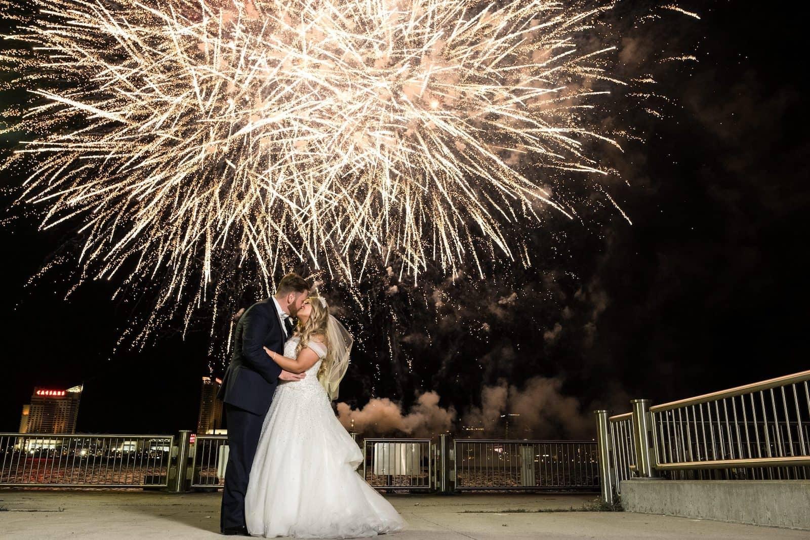 bride and groom kissing under fireworks