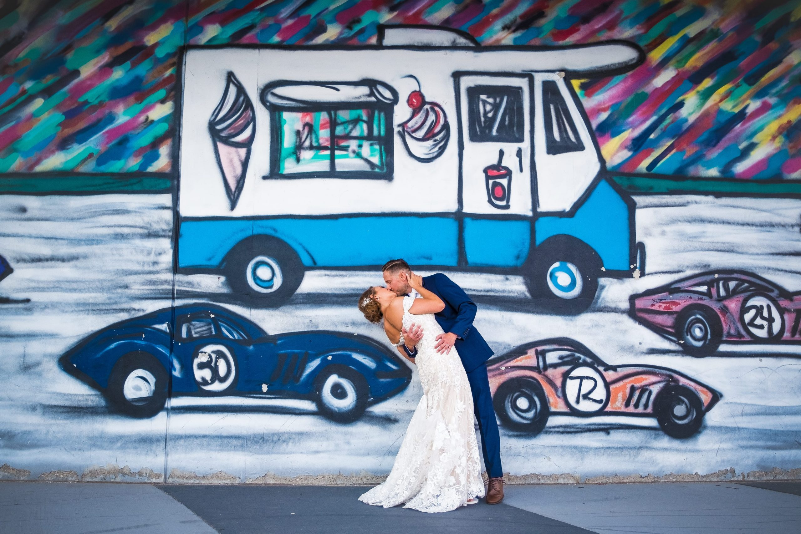 bride and groom kissing in front of detroit mural