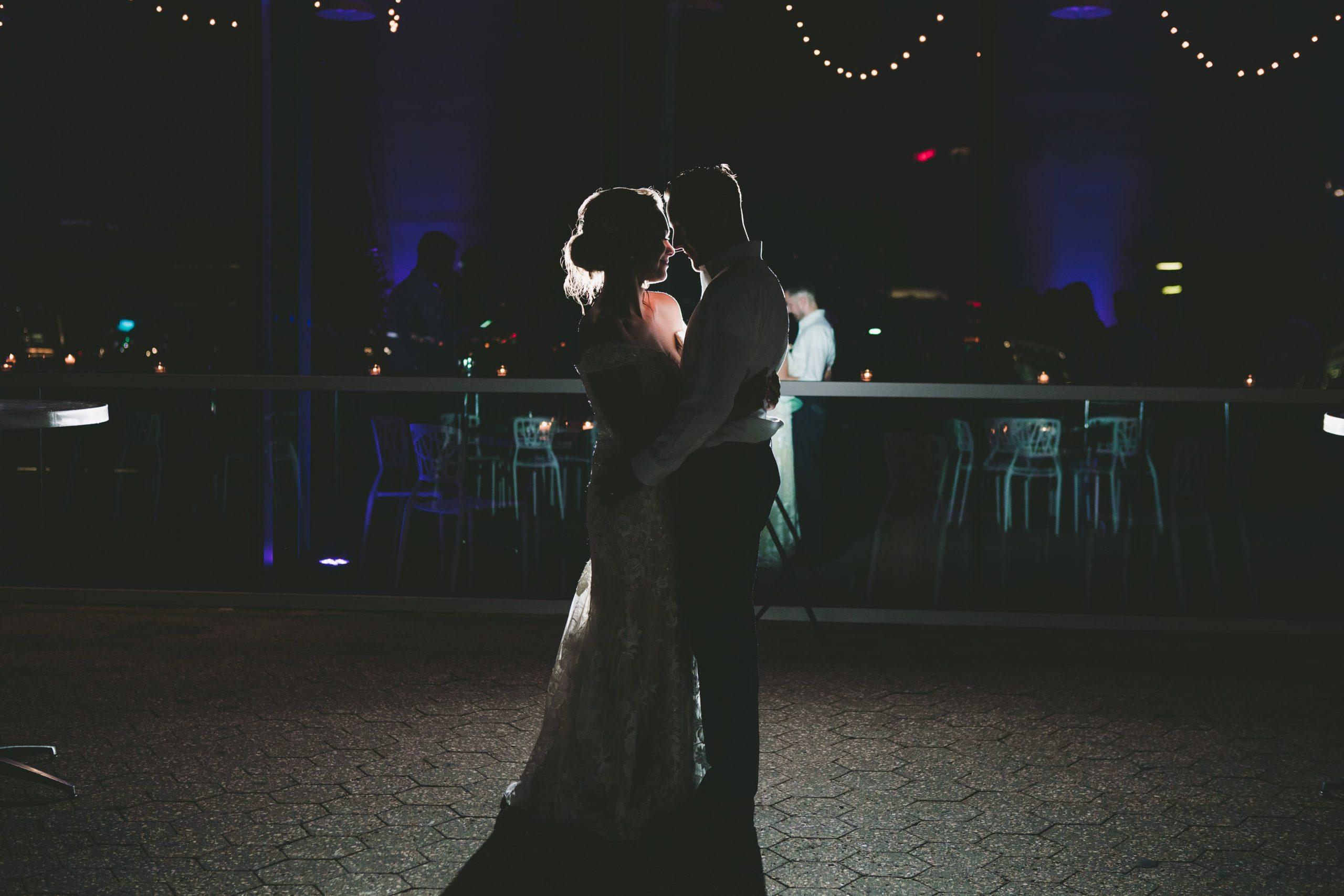 bride and groom dancing with minimal lighting