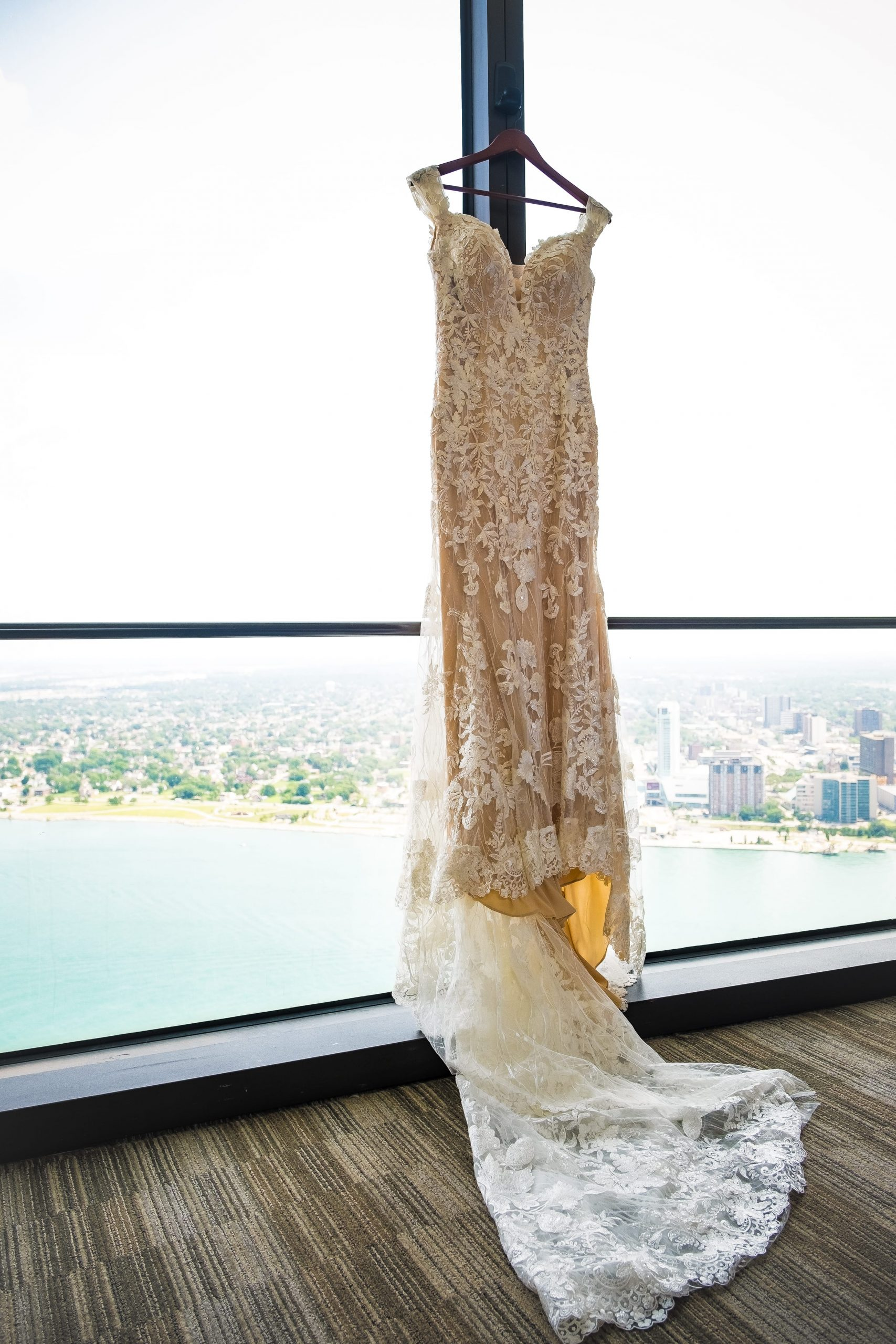 bride's gown hanging on window at detroit waterfront