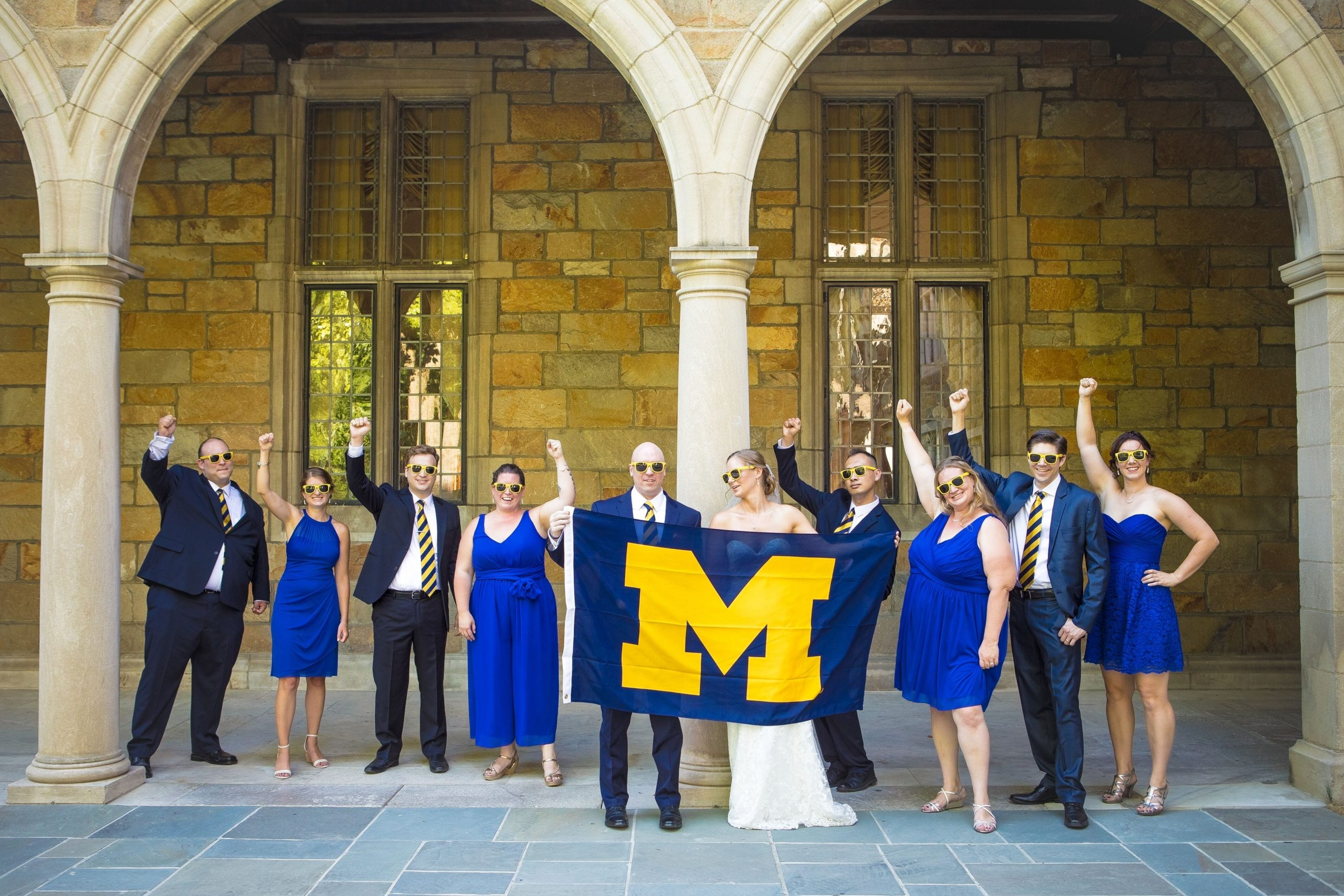 bridal party posing Michigan football flag