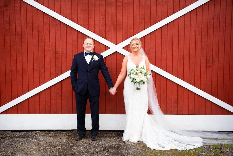 bride and groom holding hands outside barn