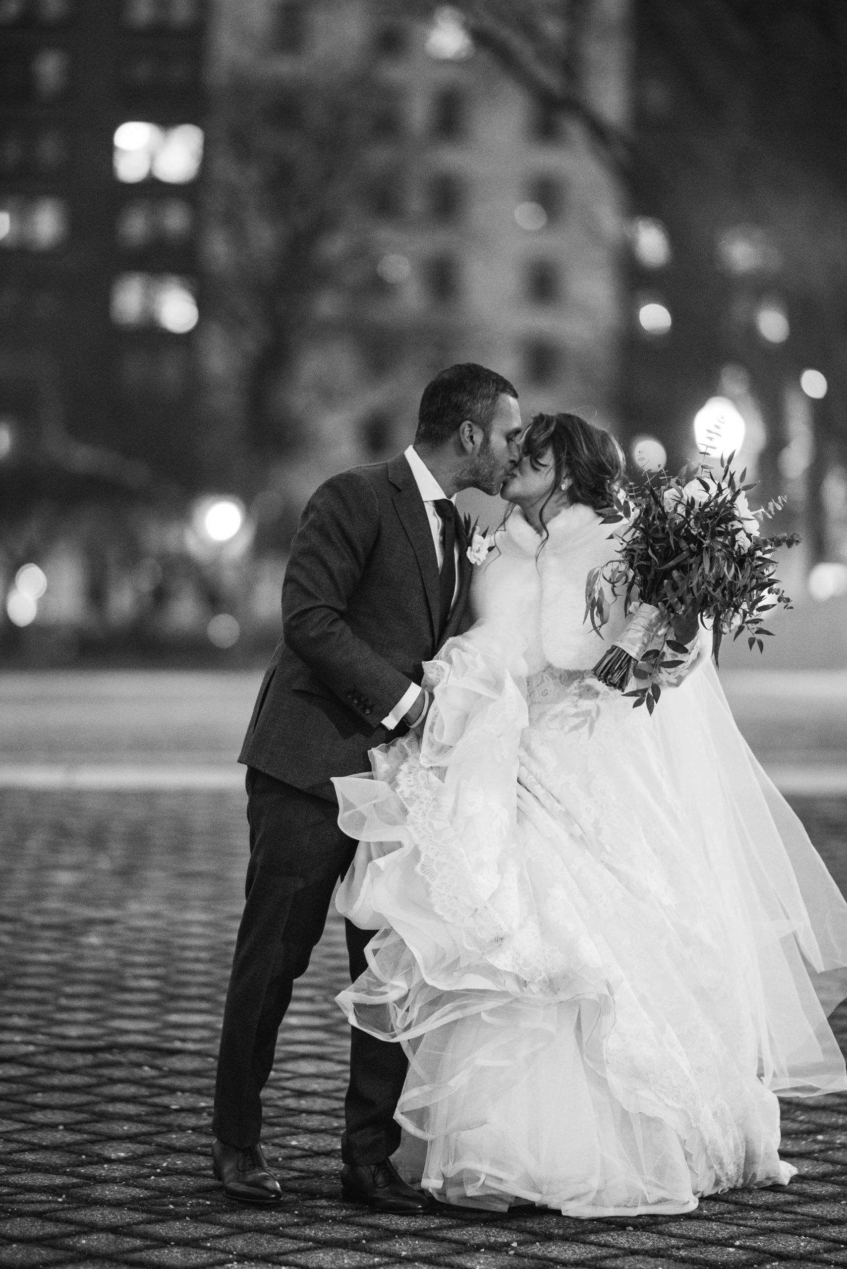 black and white photo of couple kissing downtown