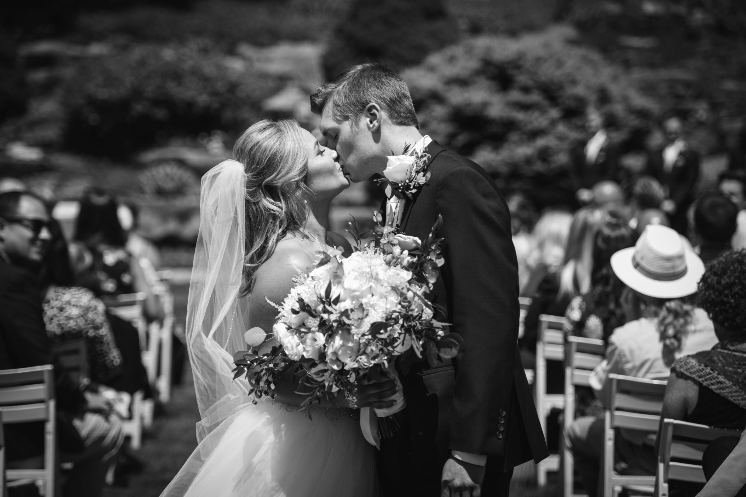 bride and groom kissing at end of aisle scaled 1