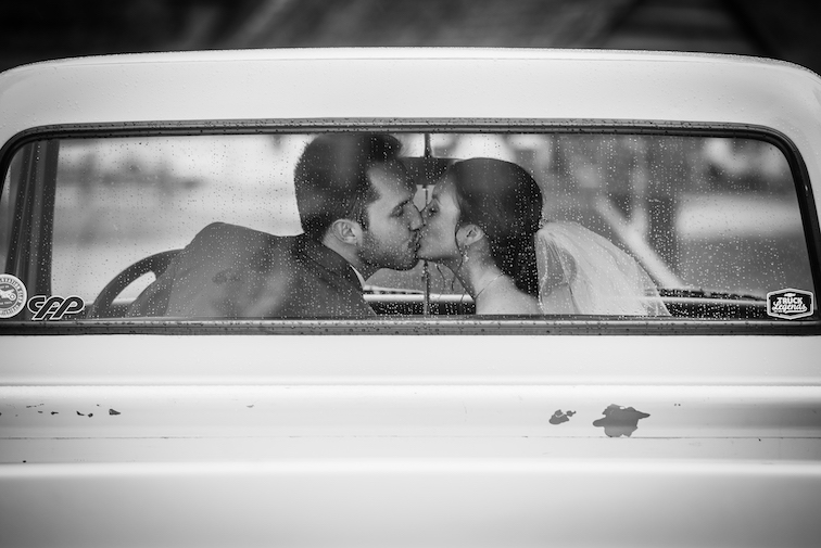 bride and groom kissing in wedding day transportation