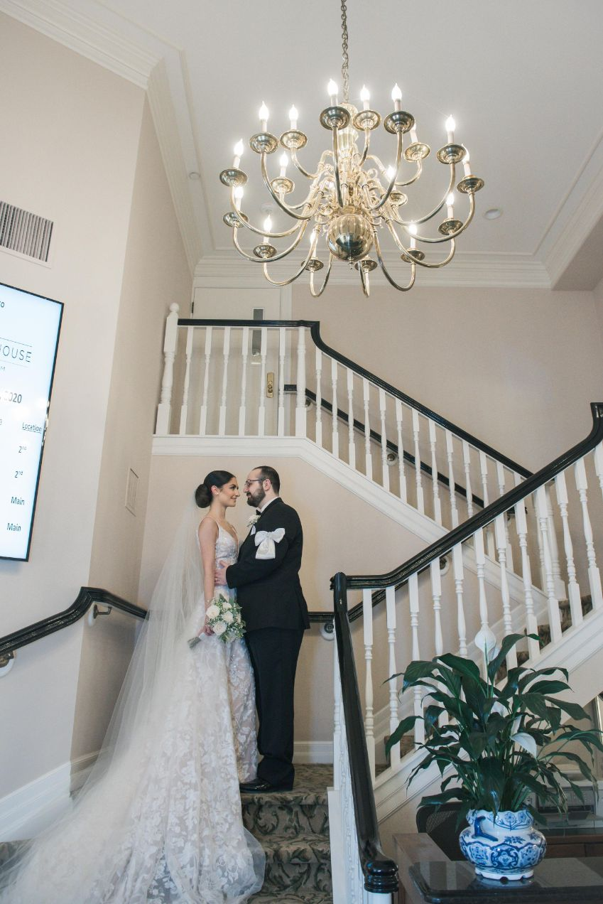 bride and groom on stairs with chandelier above