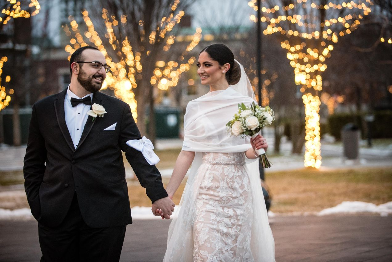 bride and groom walking outside by christmas lights