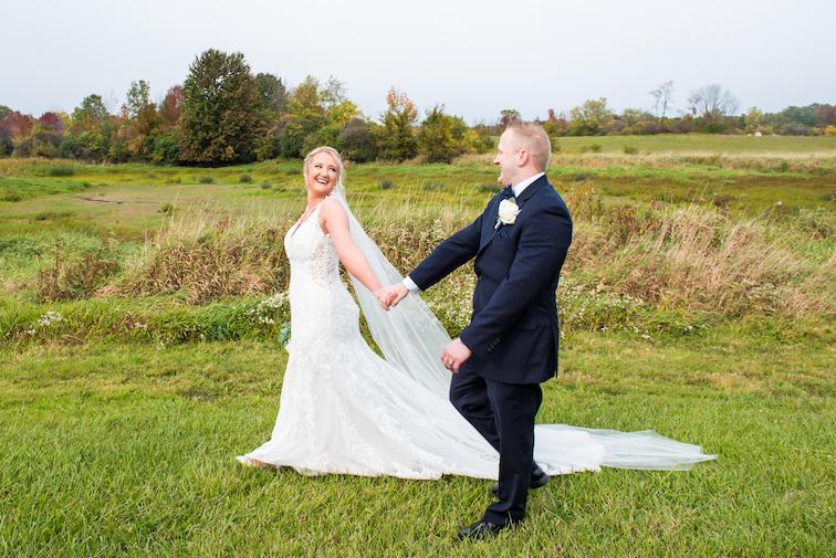 bride and groom walking through field during fall wedding