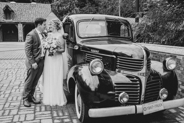 bride and groom with classic car for wedding day transportation