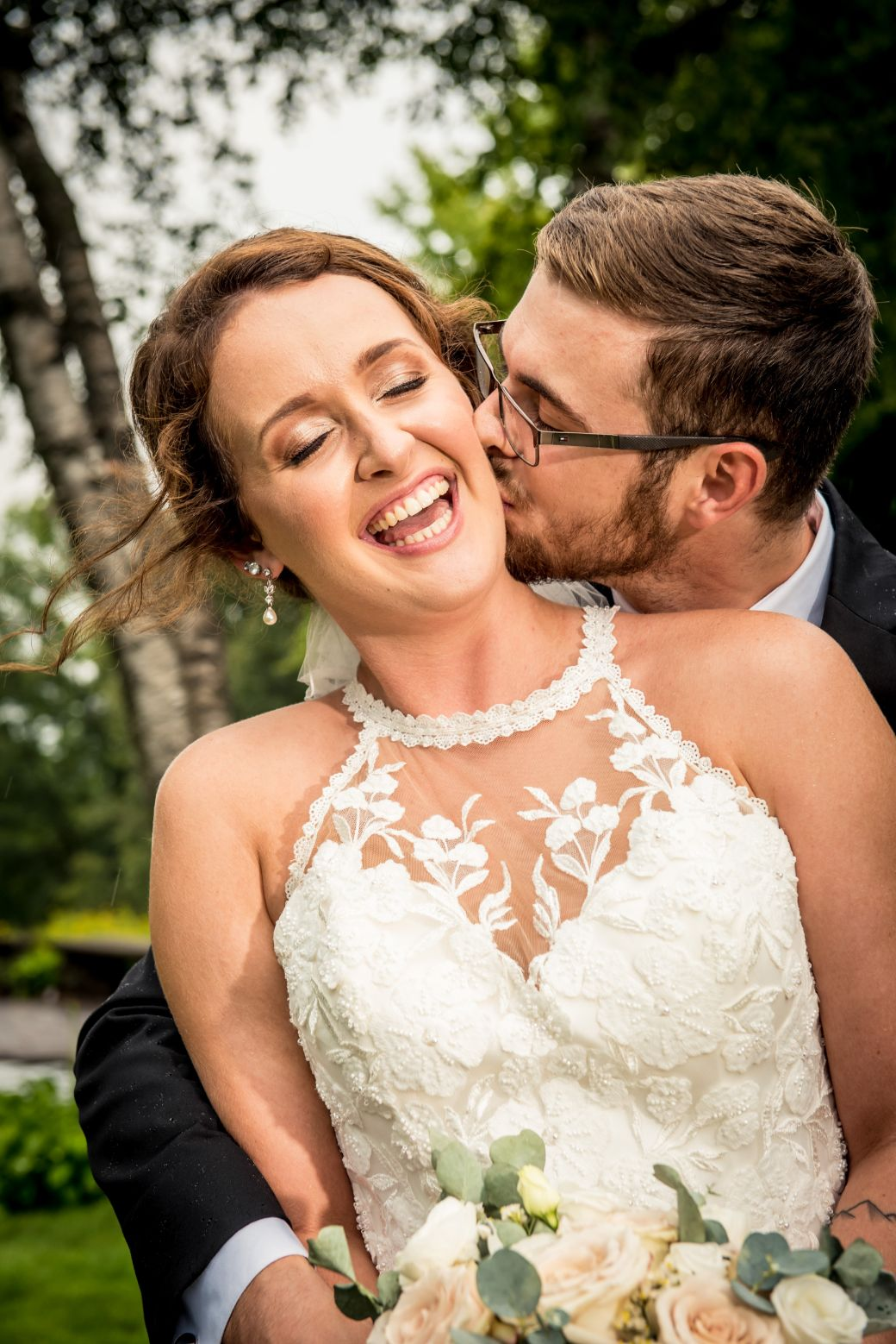 bride laughing while groom kisses her cheek
