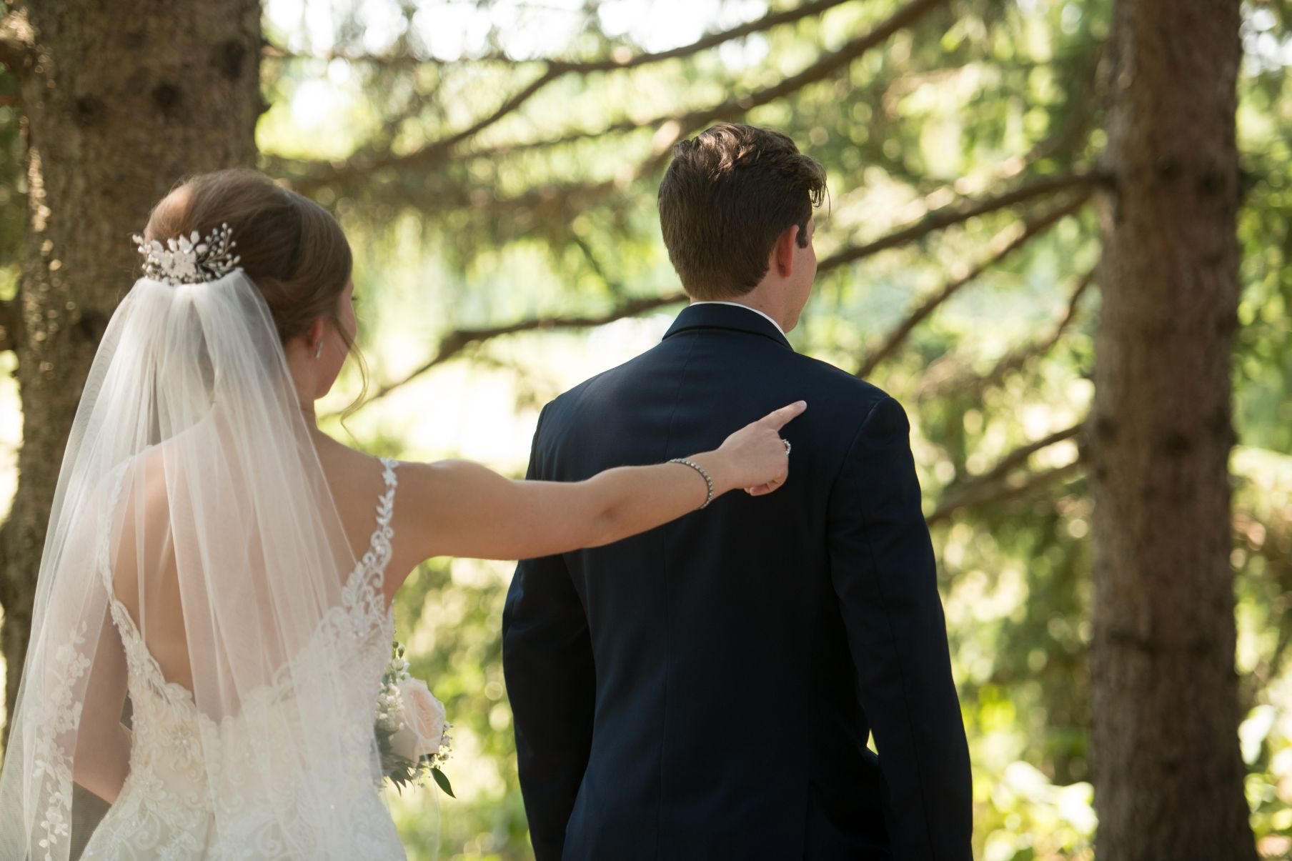 bride tapping grooms shoulder for first look